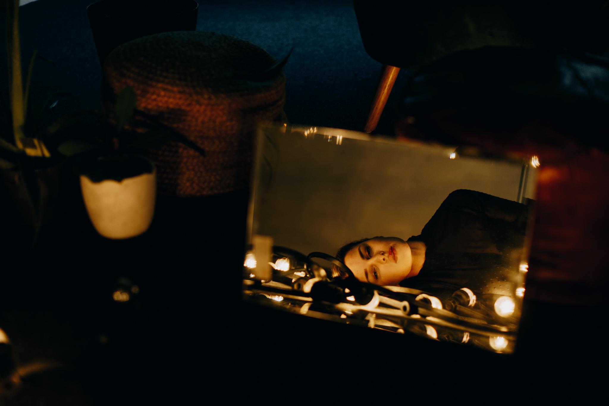 Girl looking in mirror while lying on floor