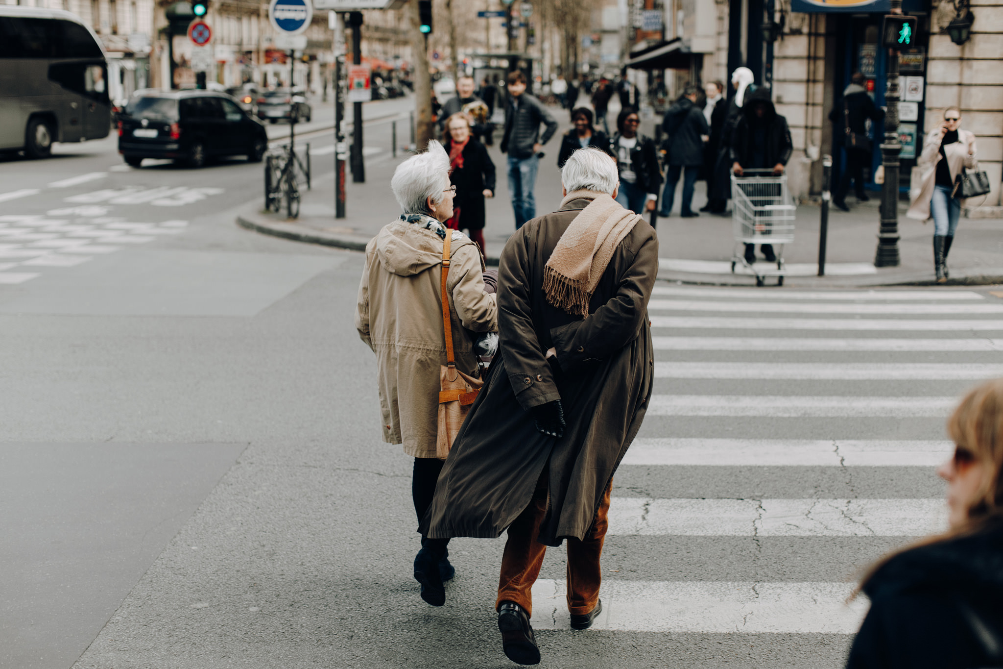 Older couple crossing street in Paris, France