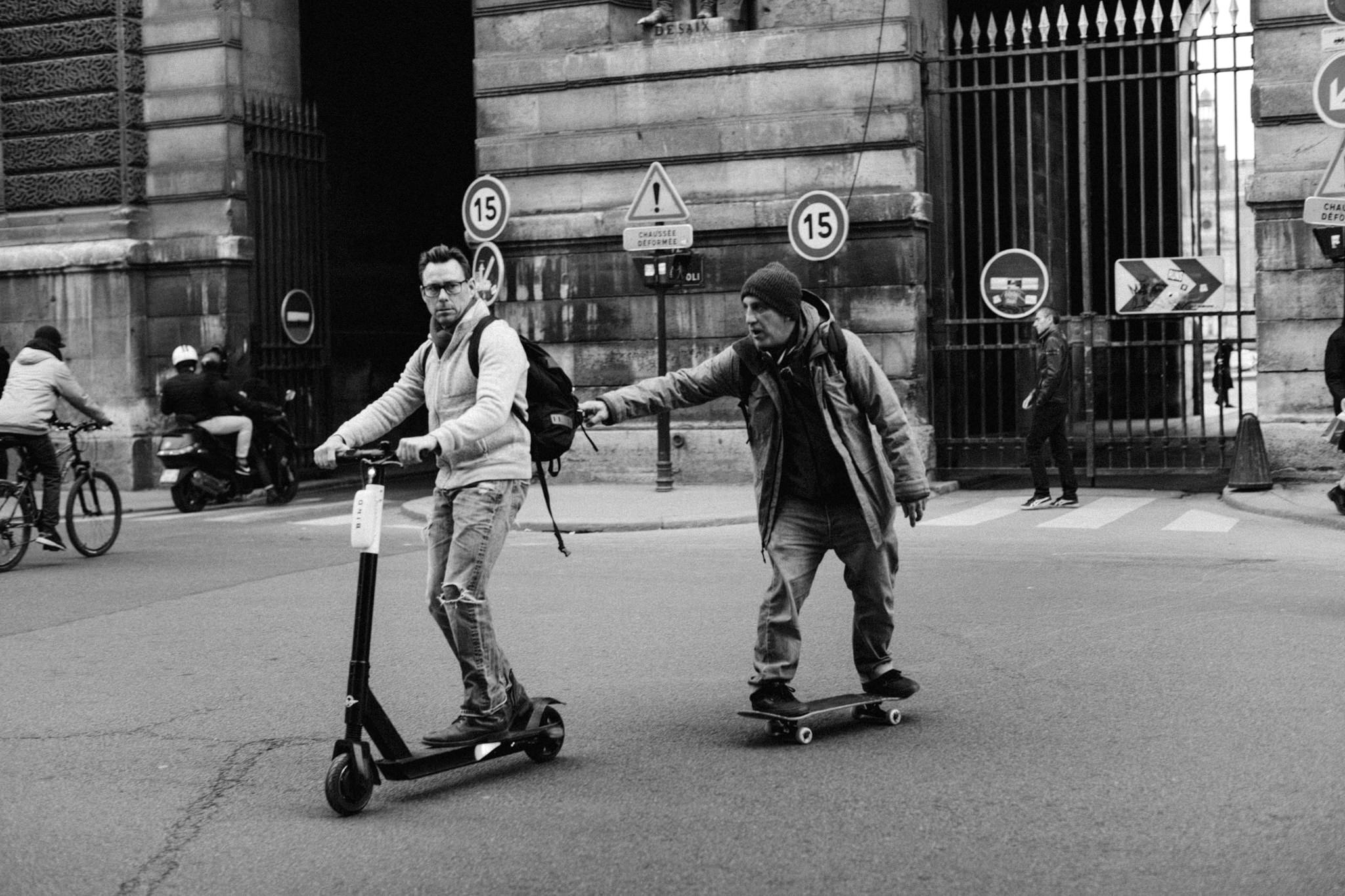 Guy on skateboard pulled by step scooter in Paris, France