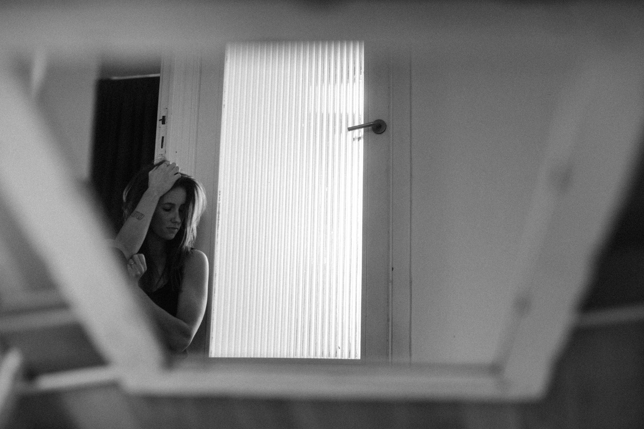 Girl sitting next to door photographed in mirror