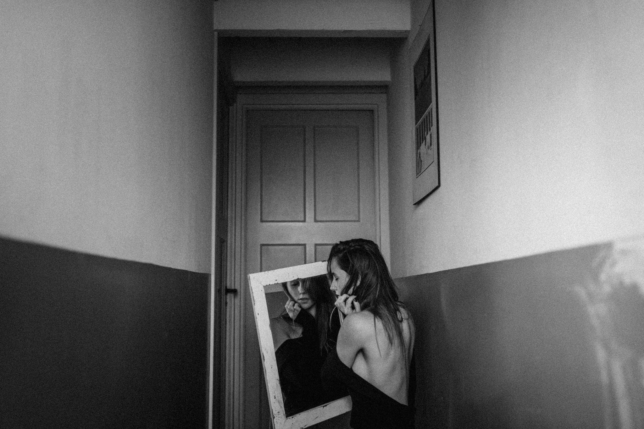 Girl holding mirror in front of door