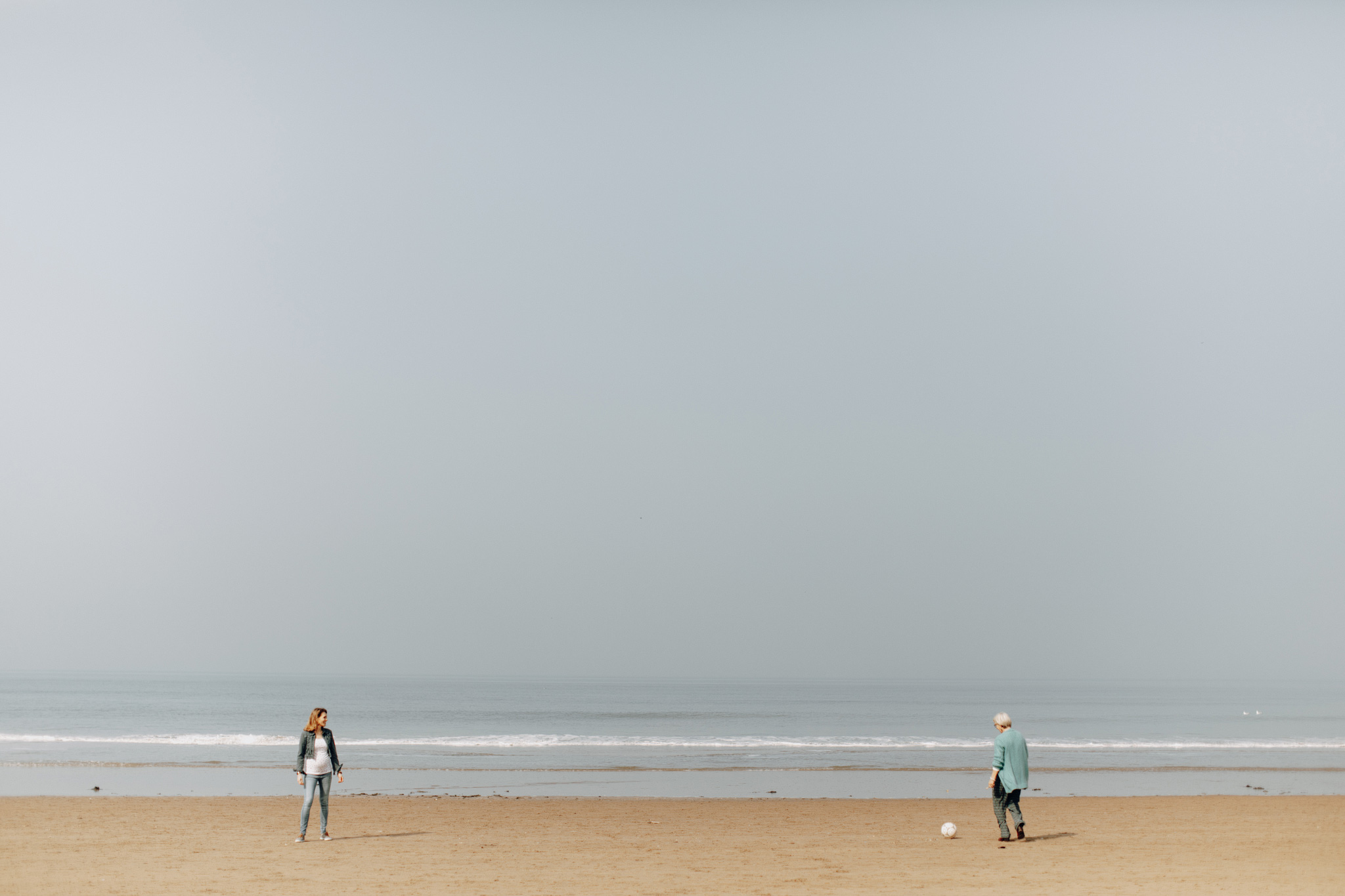 Beach shoreline with woman playing soccer