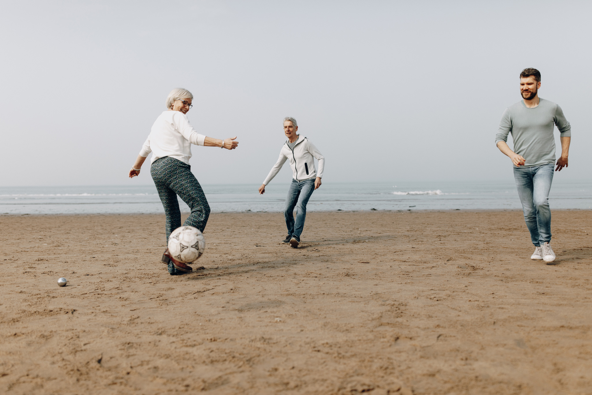 Family playing soccer at the beach