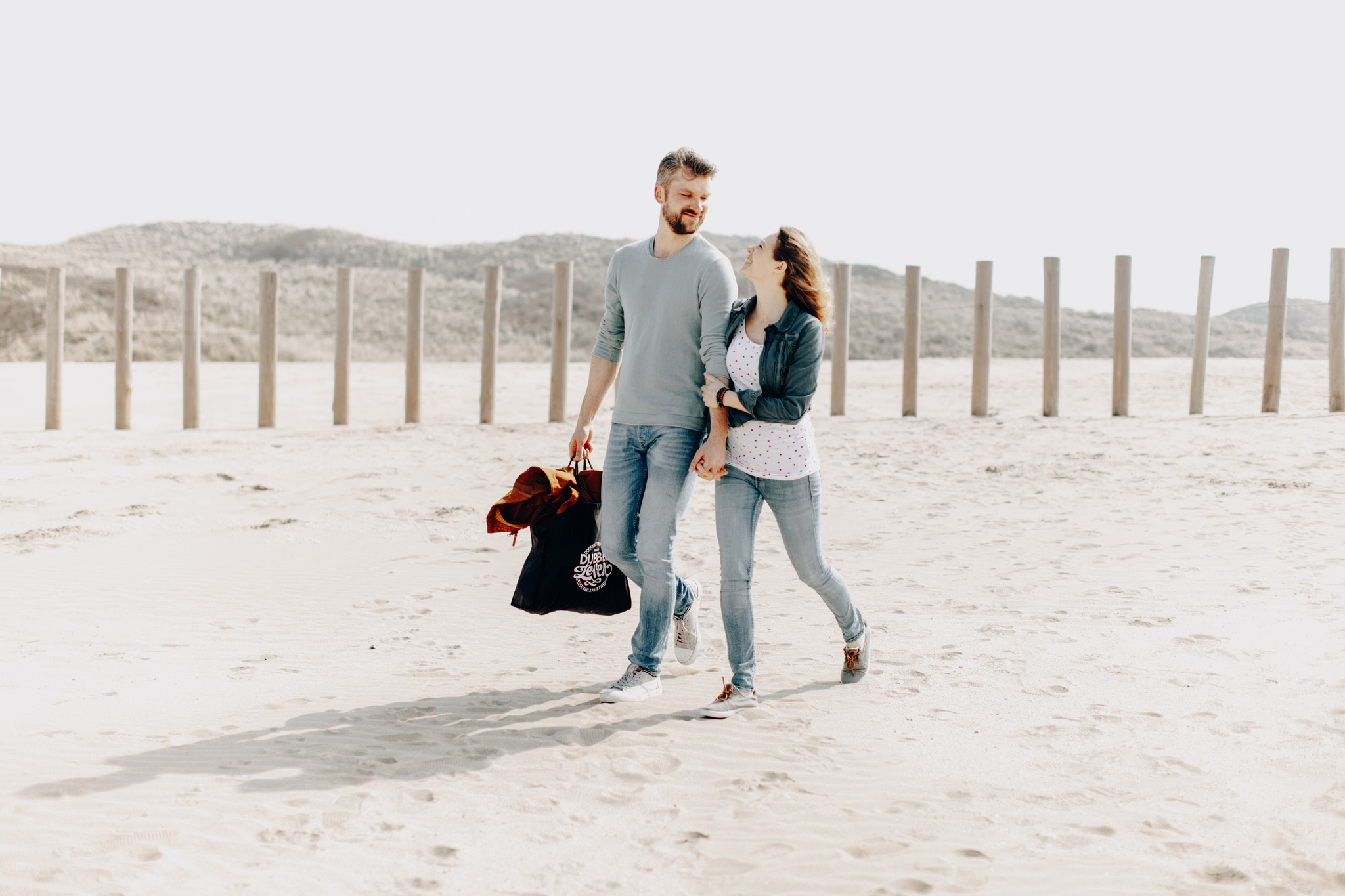 Couple walking at the beach smiling at each other