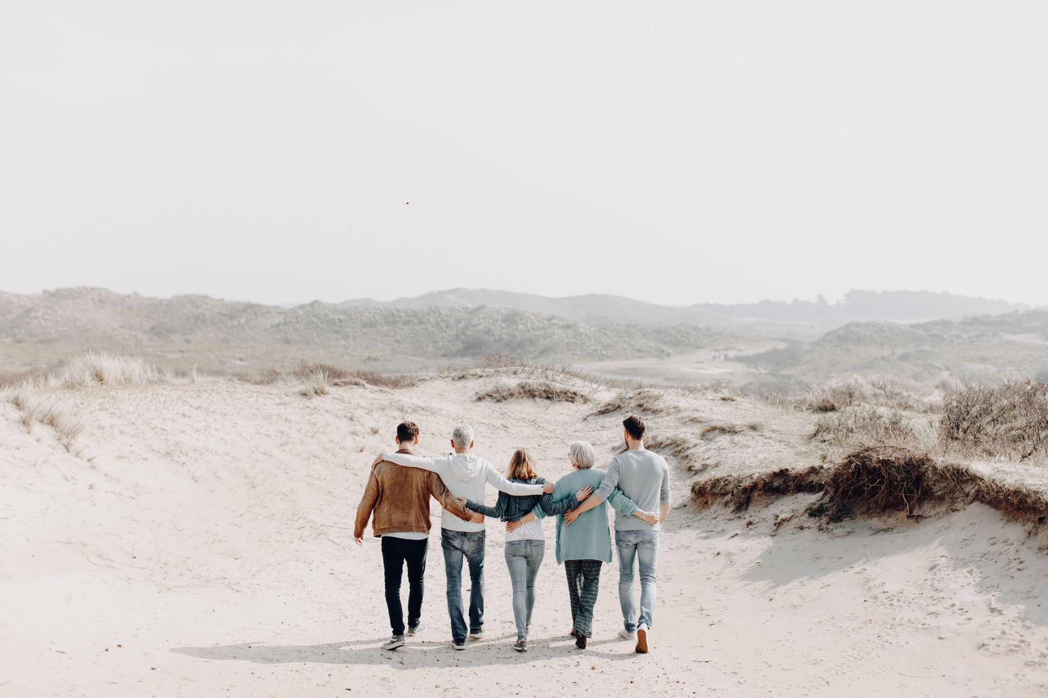 Family holding hands while walking away from camera at the dunes of Bloemendaal