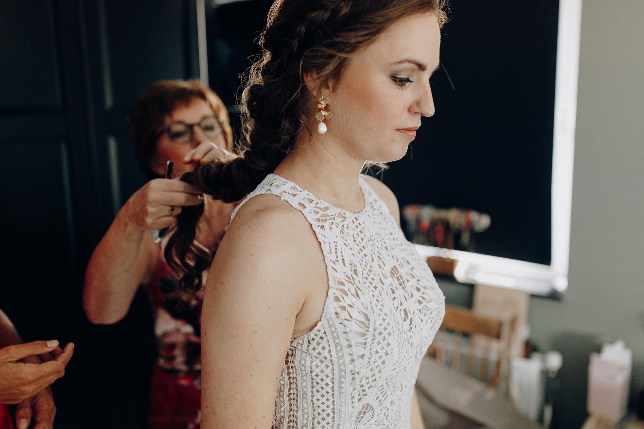 Moeder helpt bruid in Lillian West trouwjurk