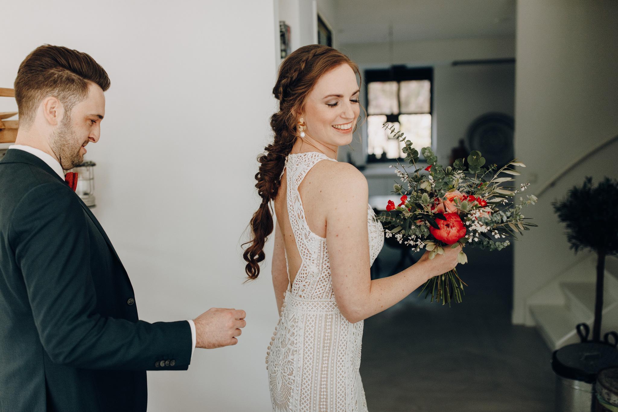 Bruidegom bekijkt achterkant Lillian West trouwjurk tijdens first look