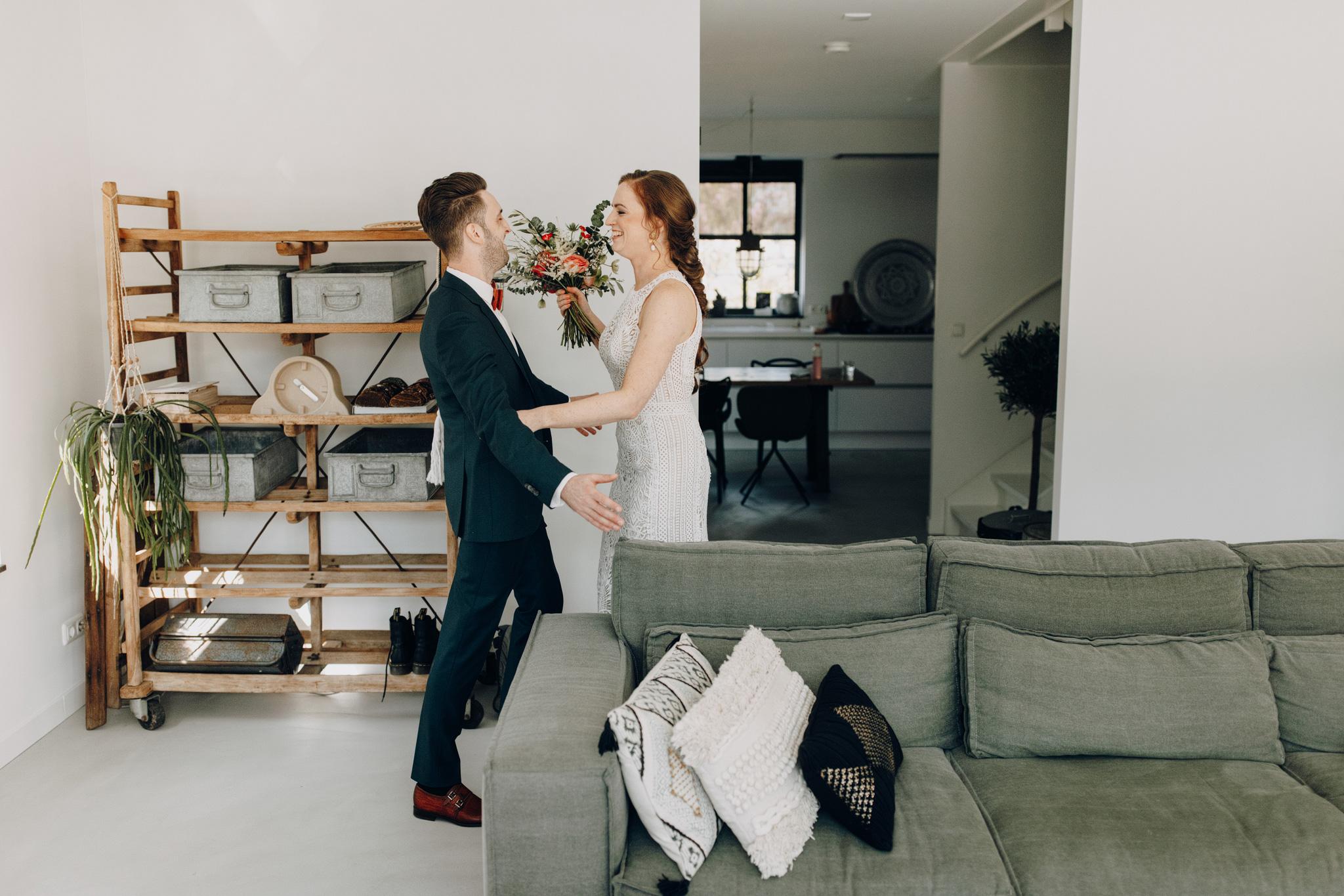 First look met bruid in Lilian West trouwjurk en bruidegom thuis