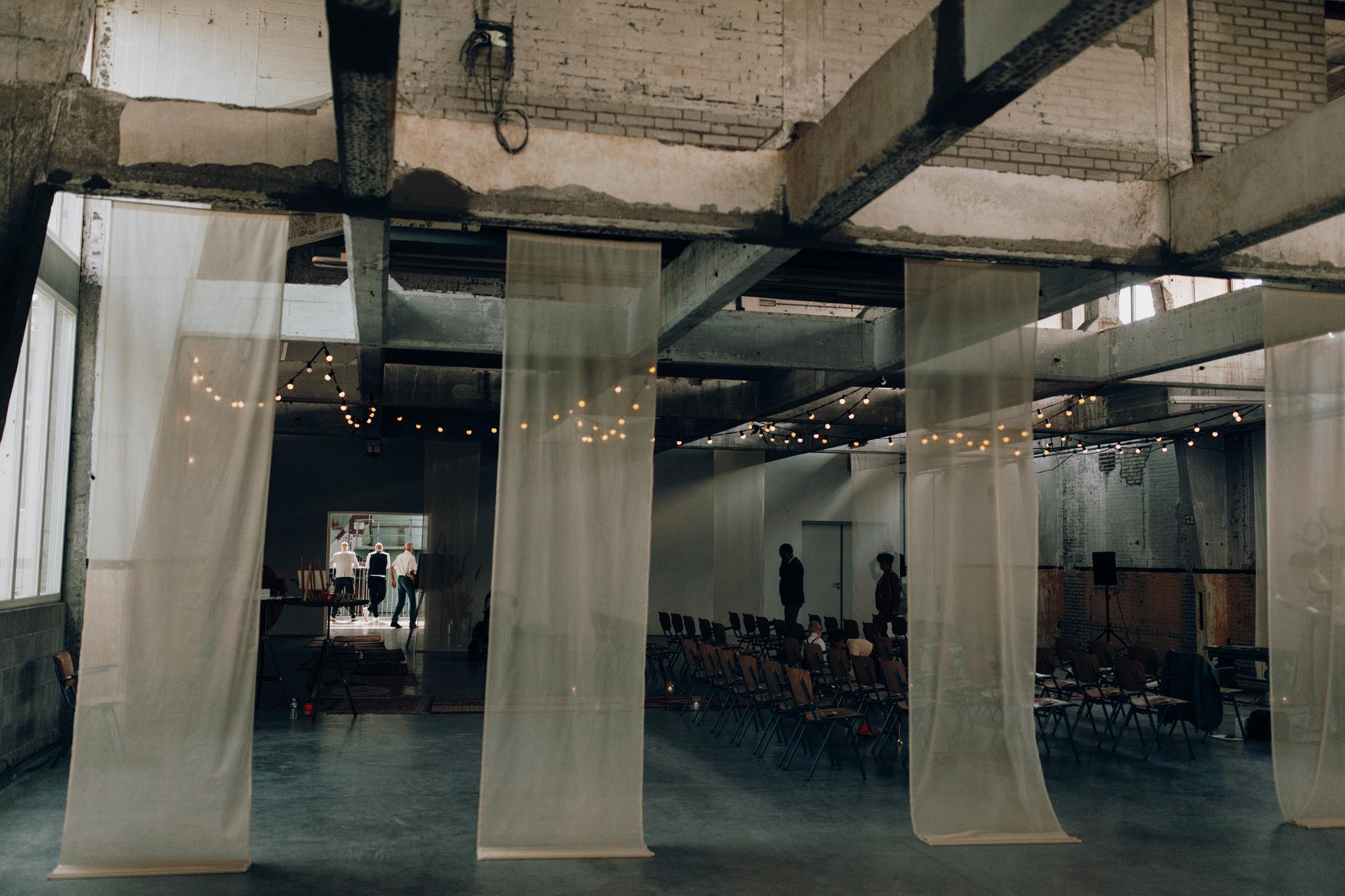 Trouw ceremonie in CHV Noordkade met hangende doeken in industriele zaal
