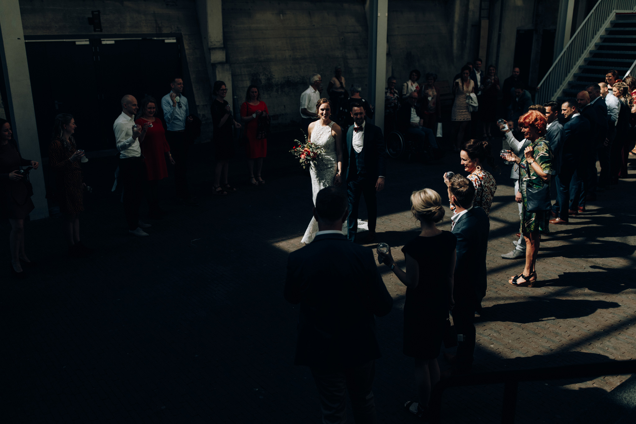 Bruid en bruidegom lopen trap af in CHV Noordkade terwijl gasten juichen