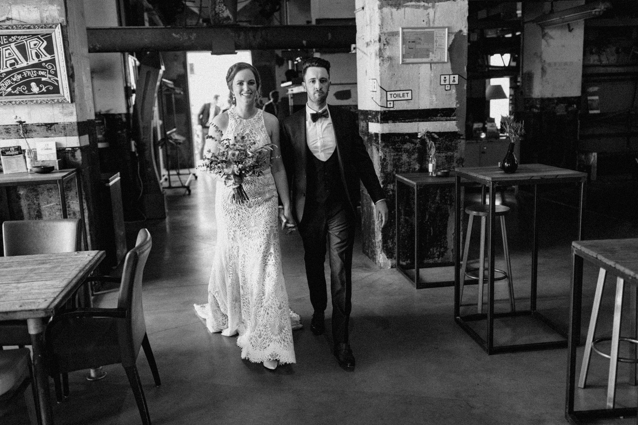 Bruid en bruidegom komen cafe Afzakkerij binnen in CHV Noordkade