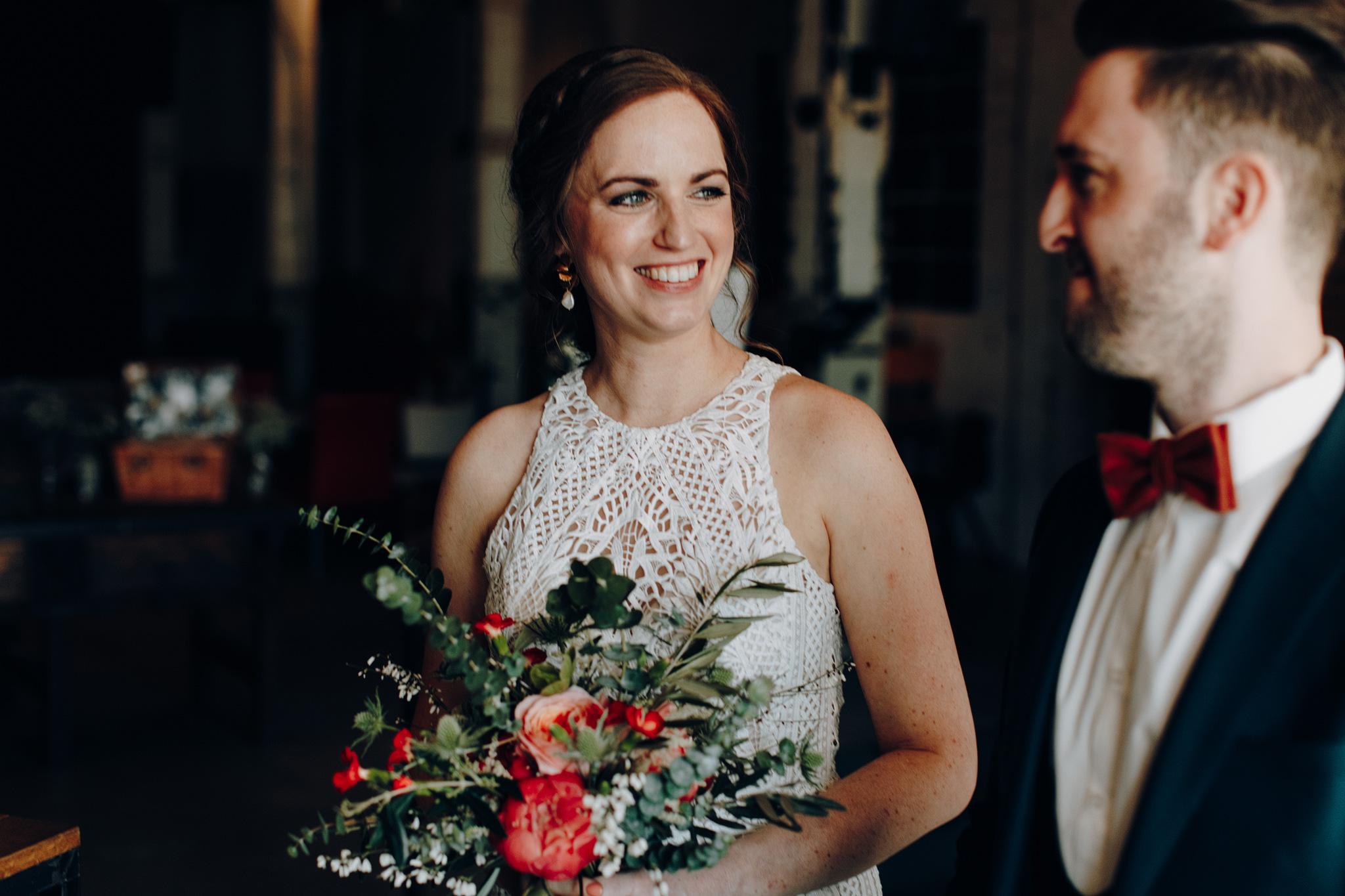 Bruid lacht naar bruidegom tijdens receptie in cafe de Afzakkerij in CHV Noordkade
