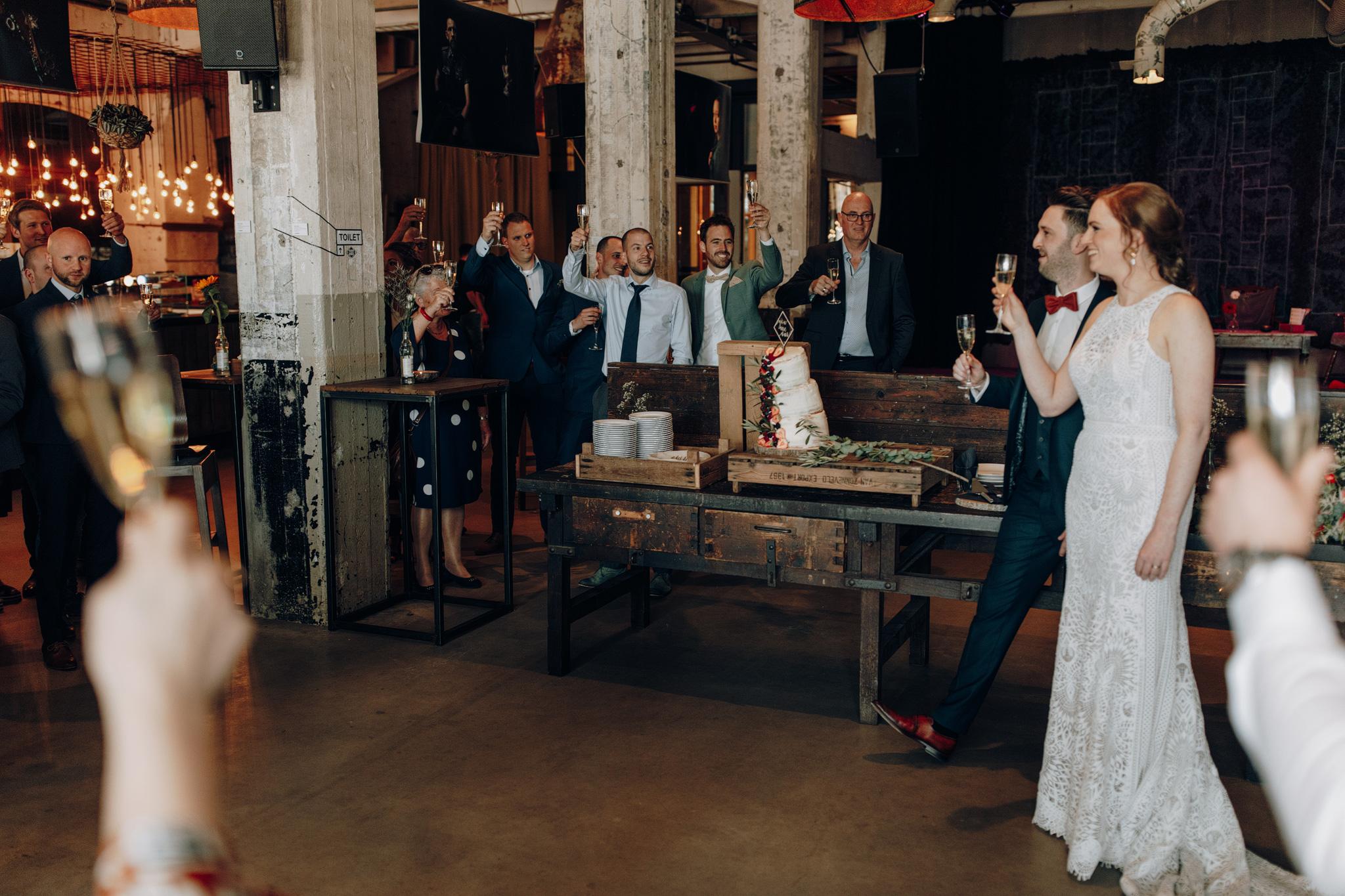 Bruid en bruidegom proosten in cafe de Afzakkerij in CHV Noordkade