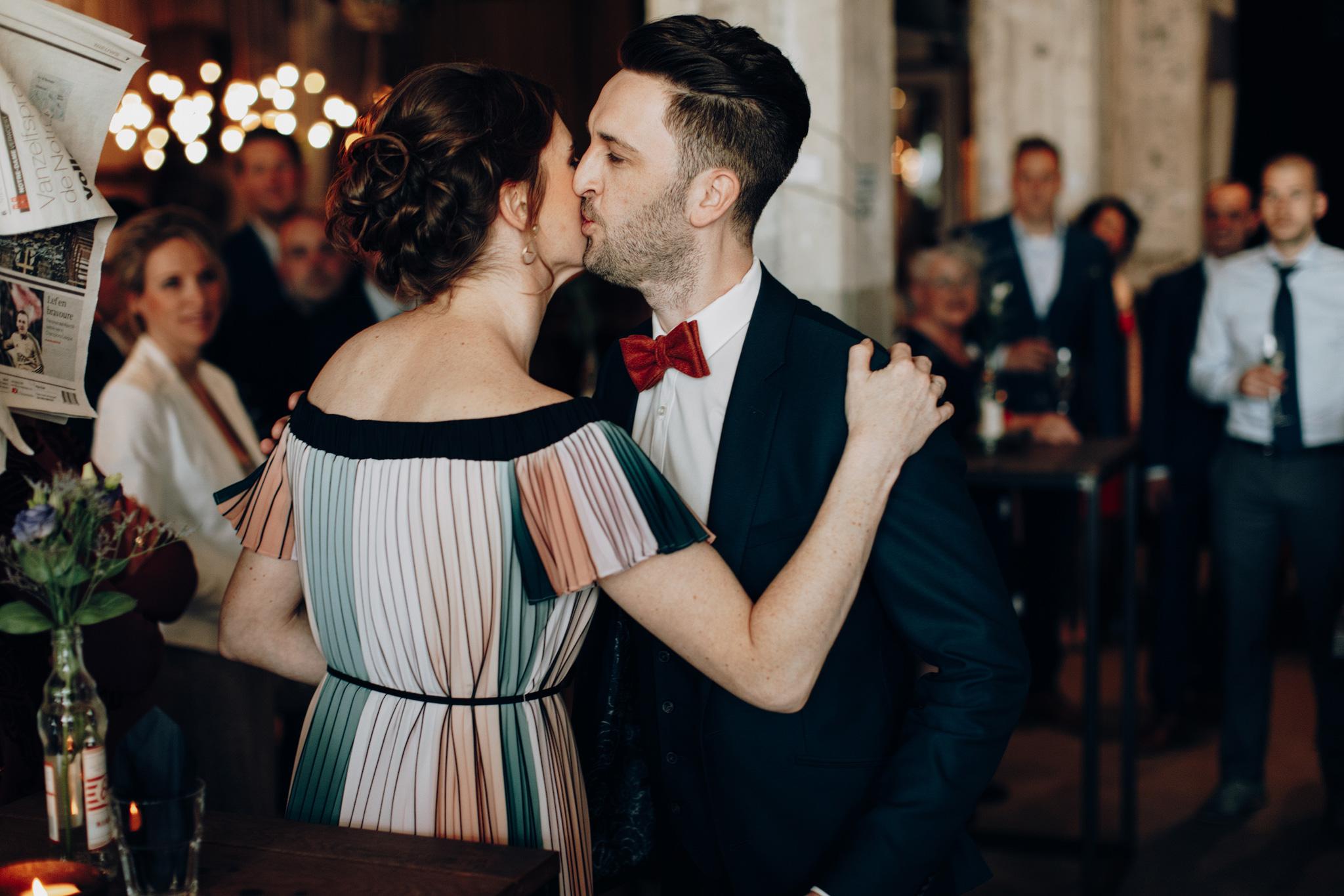 Bruidegom geeft kus aan gast tijdens receptie trouwerij