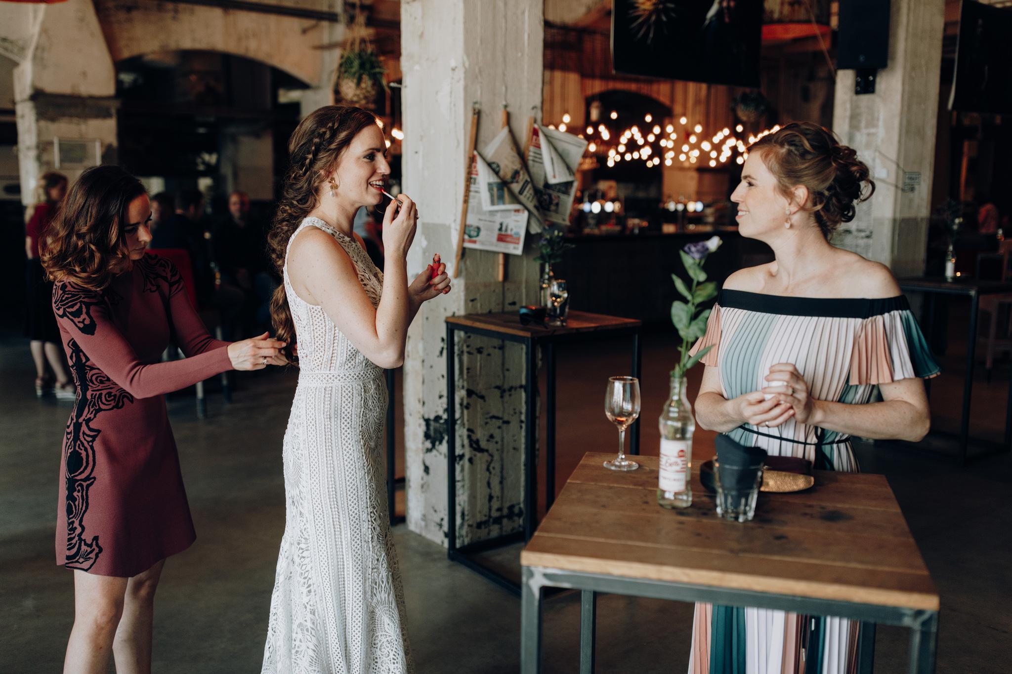 Bruid doet make-up voor de fotoshoot
