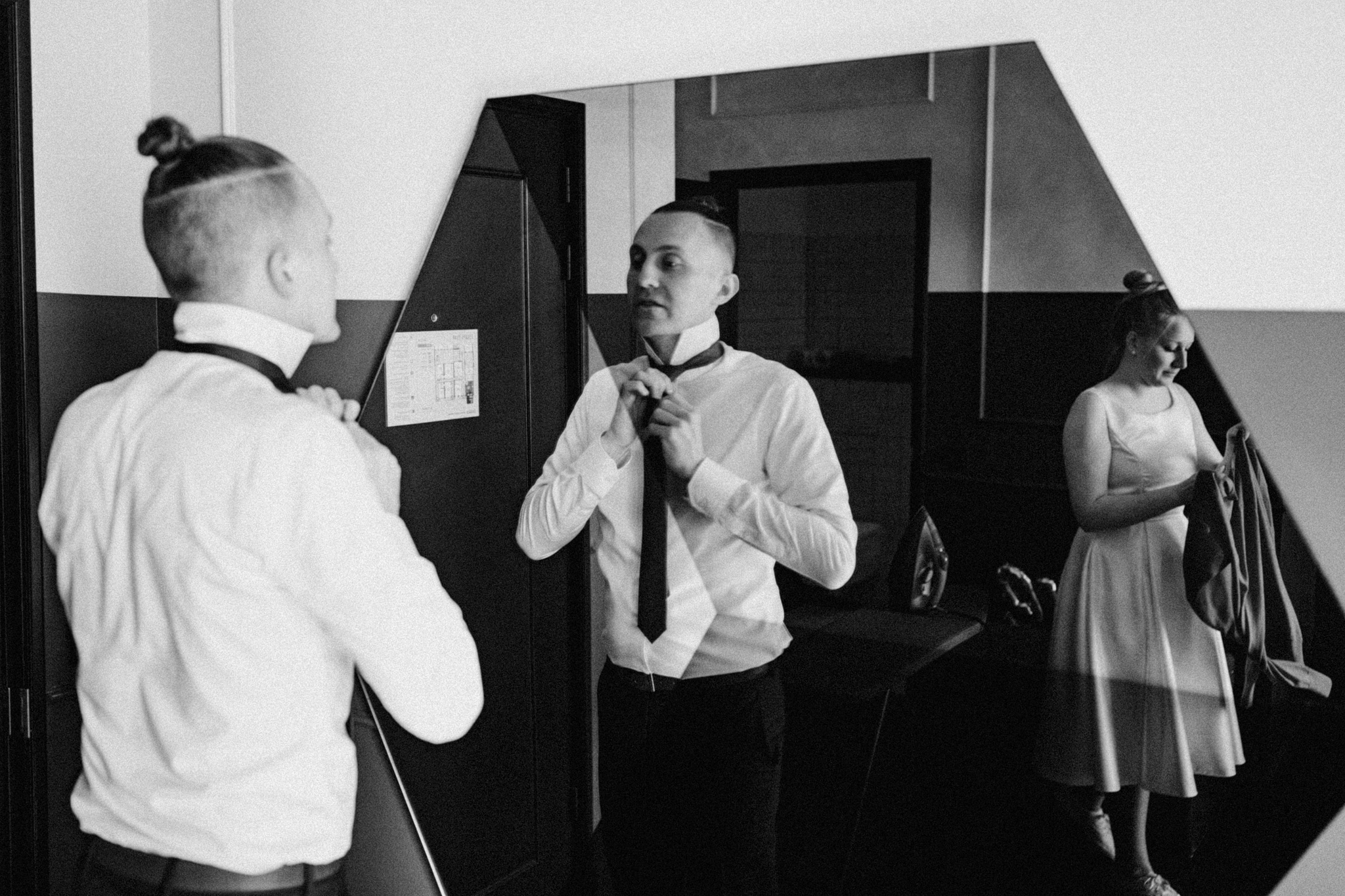 Groom tying his tie with bride in the mirror