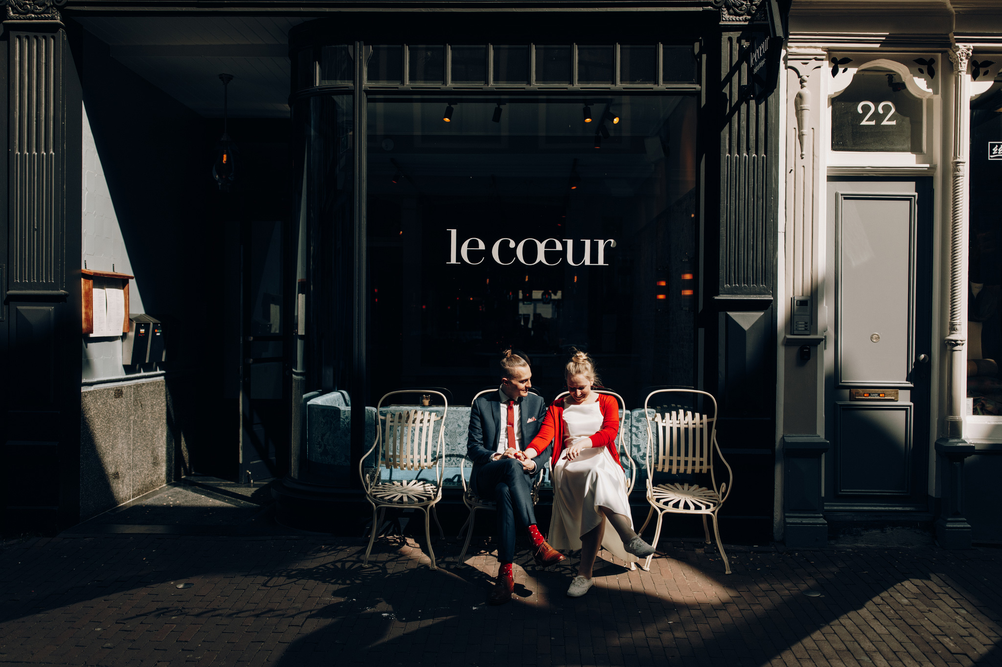 Elopement couple sitting on bench in sunlight on the streets of Amsterdam