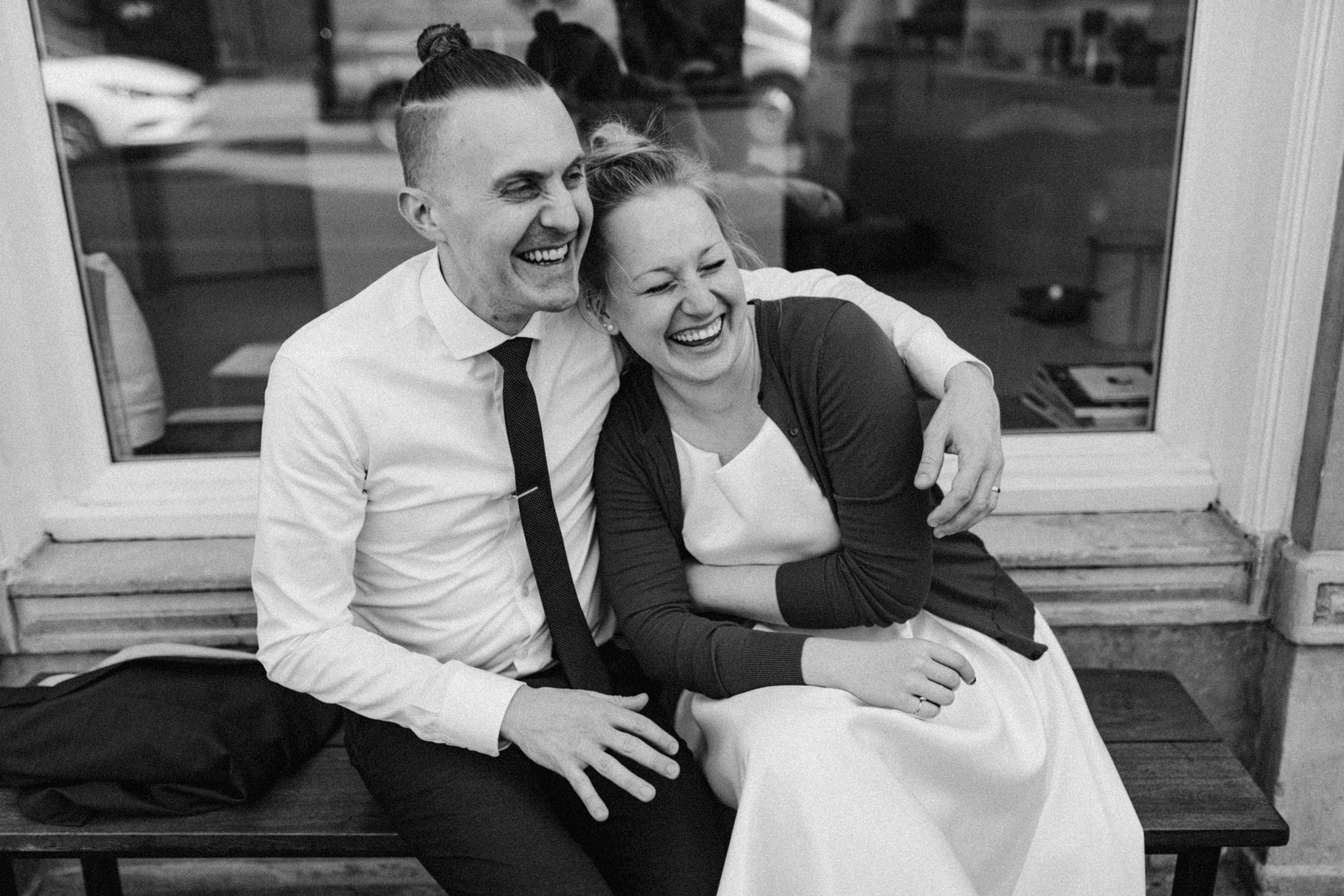 Elopement couple hugging and laughing while sitting on bench