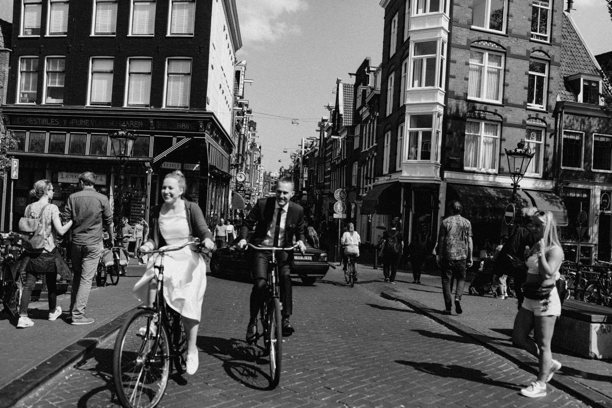 Elopement couple riding rental bikes through the streets of Amsterdam