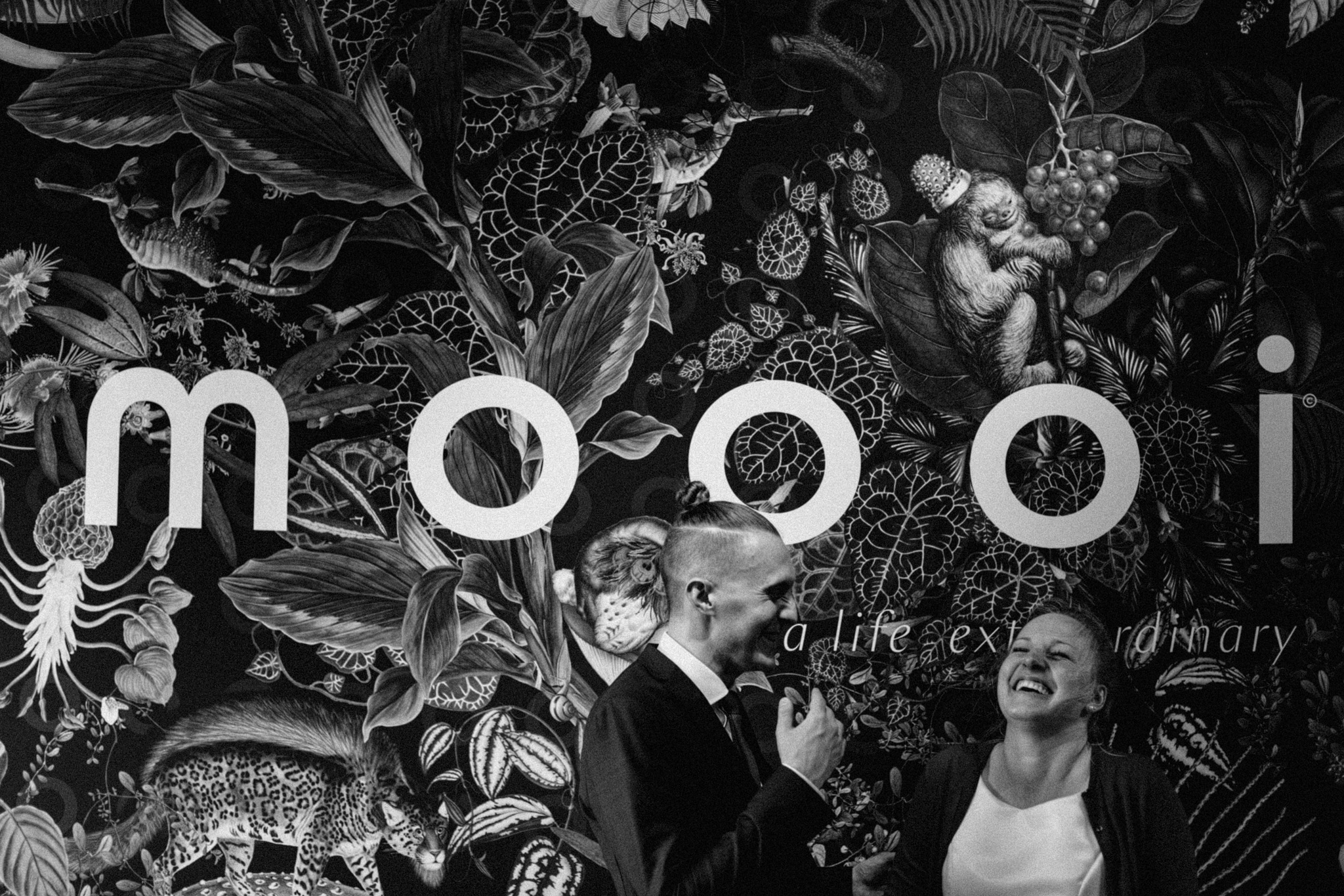 Elopement couple standing in front of big poster that says moooi