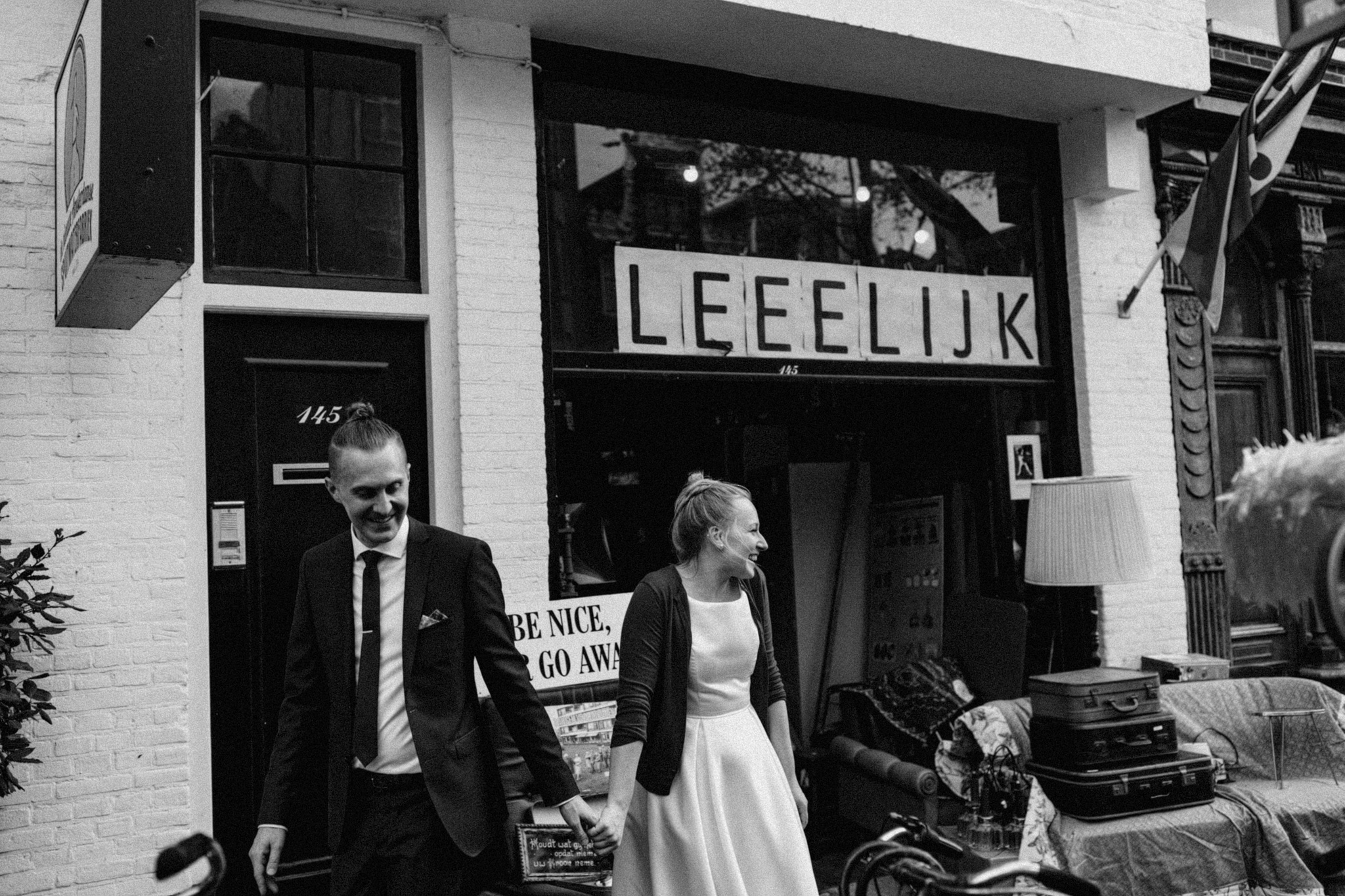 Elopement couple holding hands while walking and smiling in the Jordaan Amsterdam