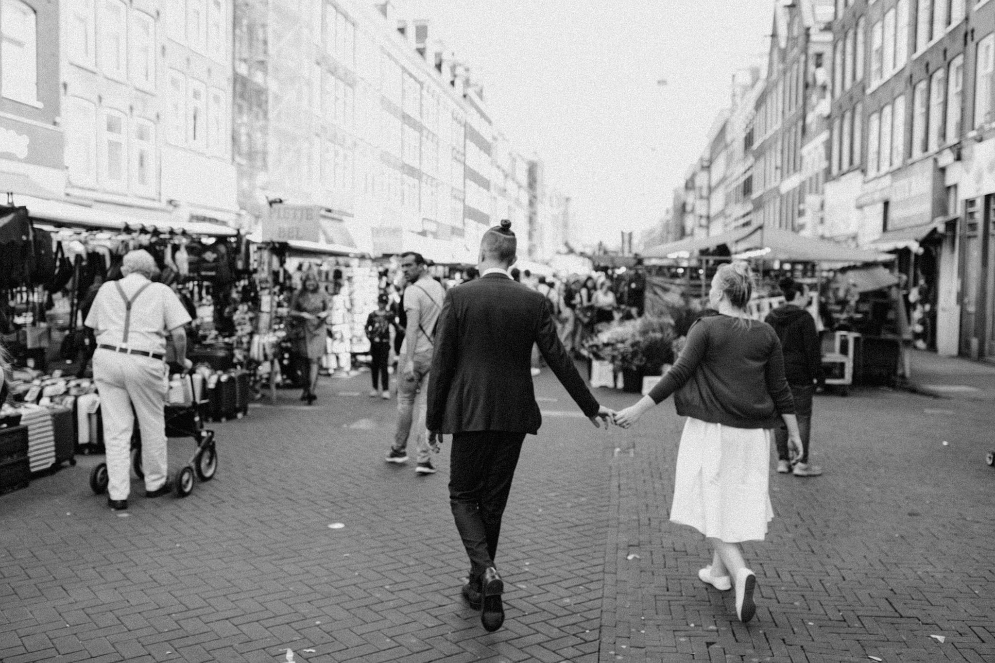 Elopement couple walking hand in hand at Albert Cuyp market Amsterdam