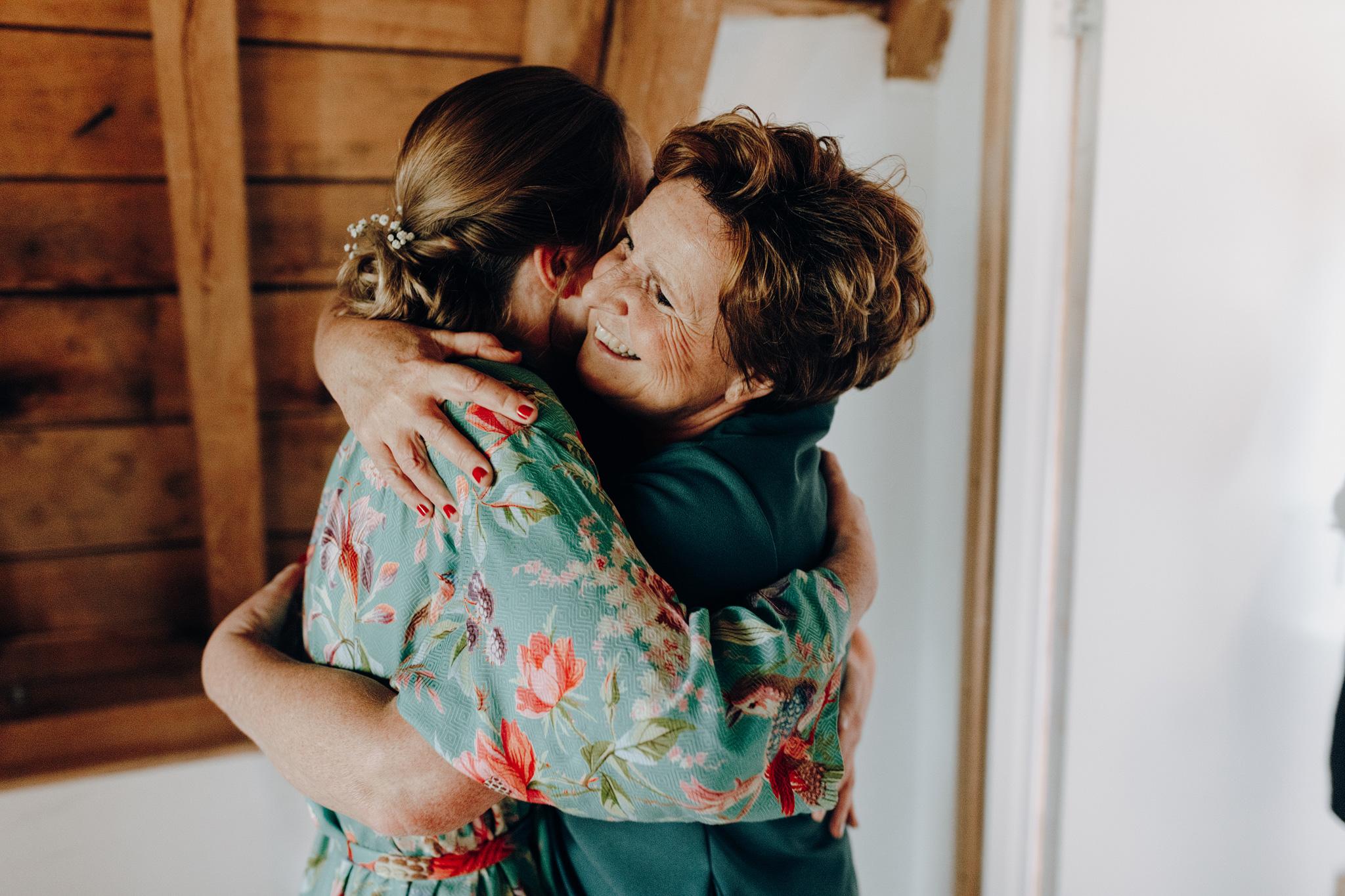Moeder van de bruid knuffelt bruid