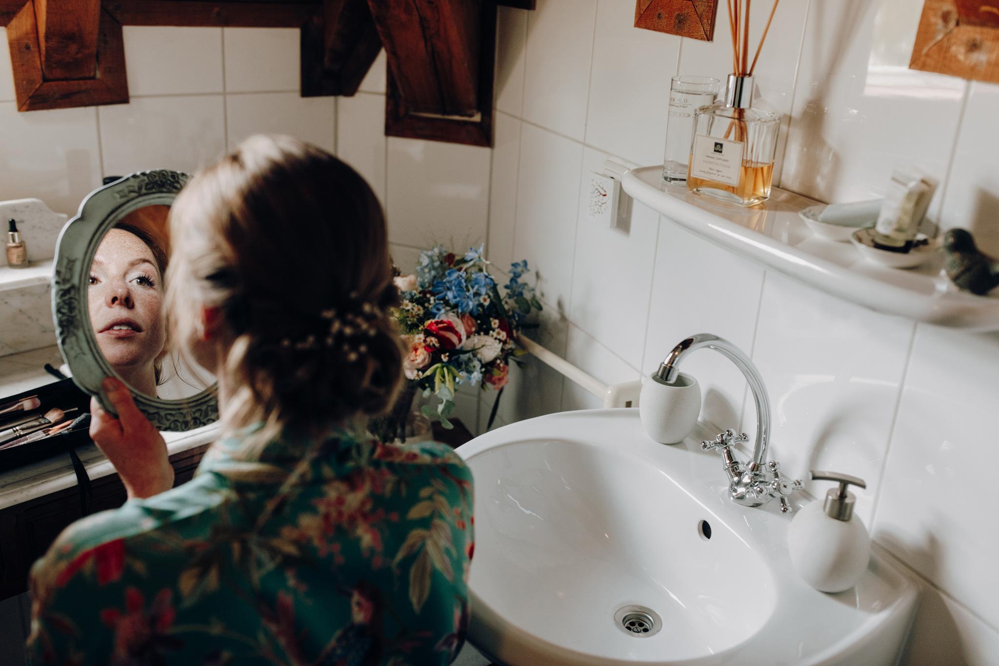 Bruid kijkt in spiegel tijdens make-up voorbereidingen op Kloster Graefenthal