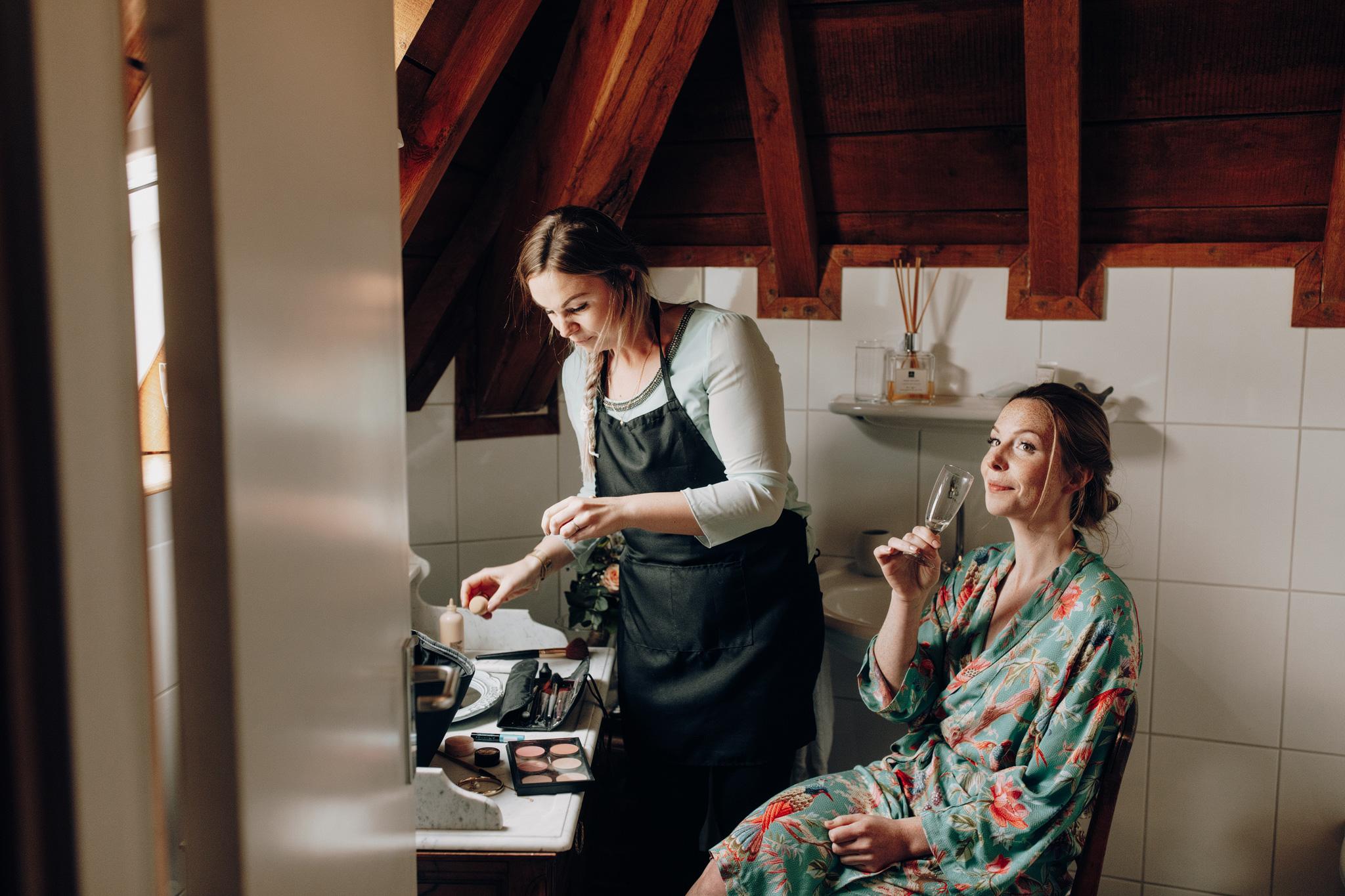 Bruid drinkt champagne tijdens make-up voorbereidingen