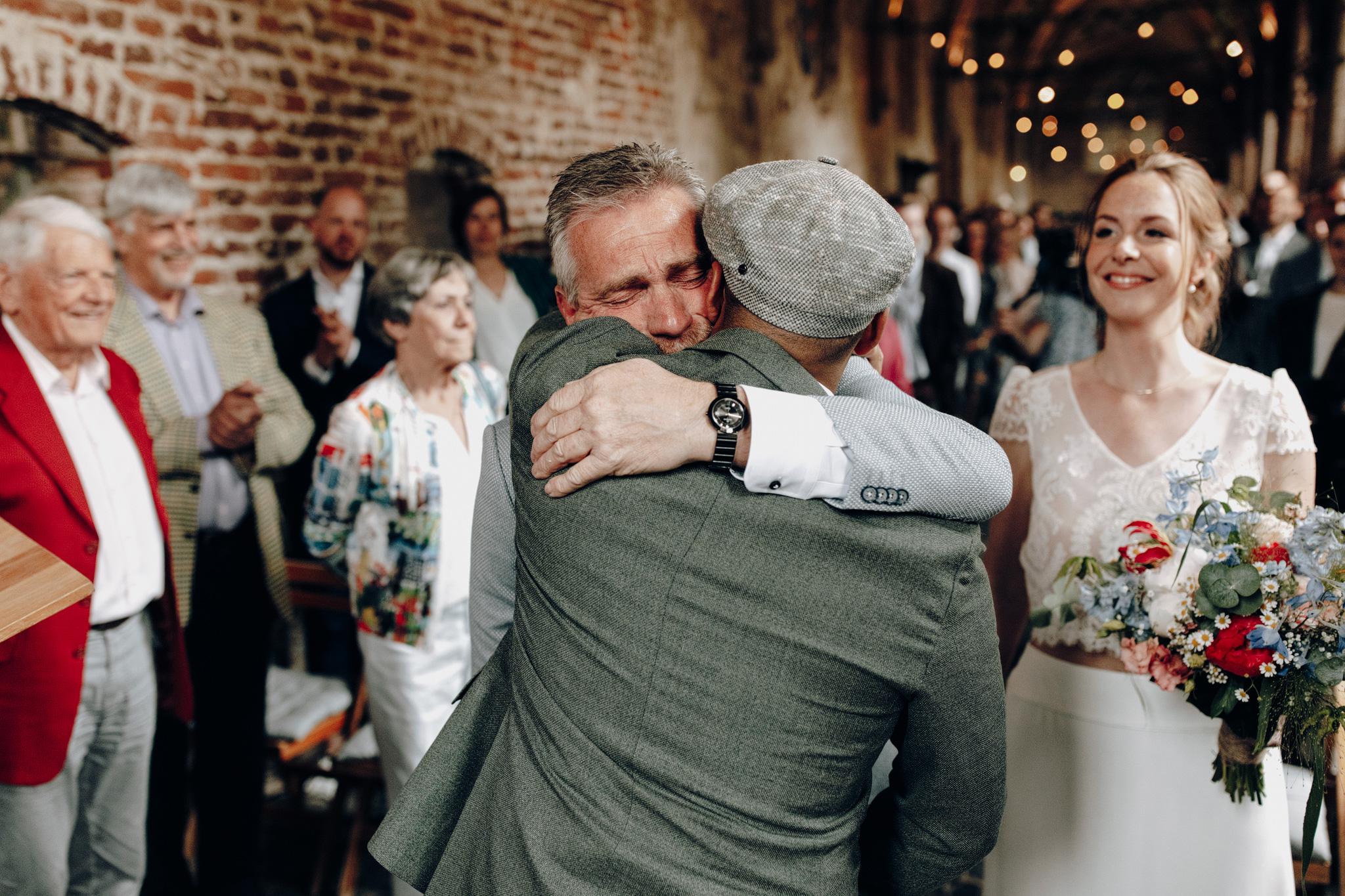 Vader bruid knuffelt bruidegom bij trouwceremonie Kloster Graefenthal