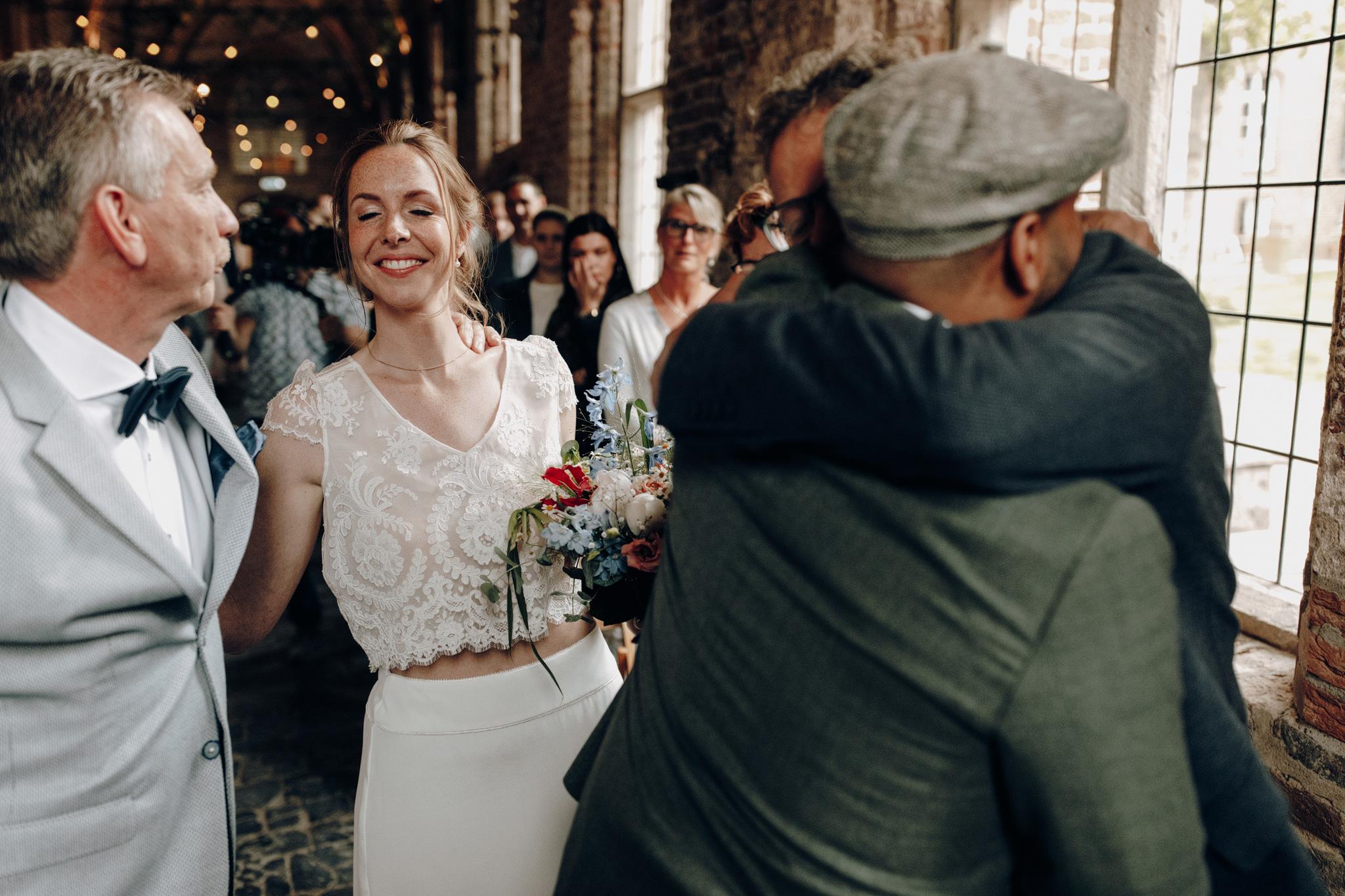 Bruid lacht naar vader tijdens trouwceremonie Kloster Graefenthal