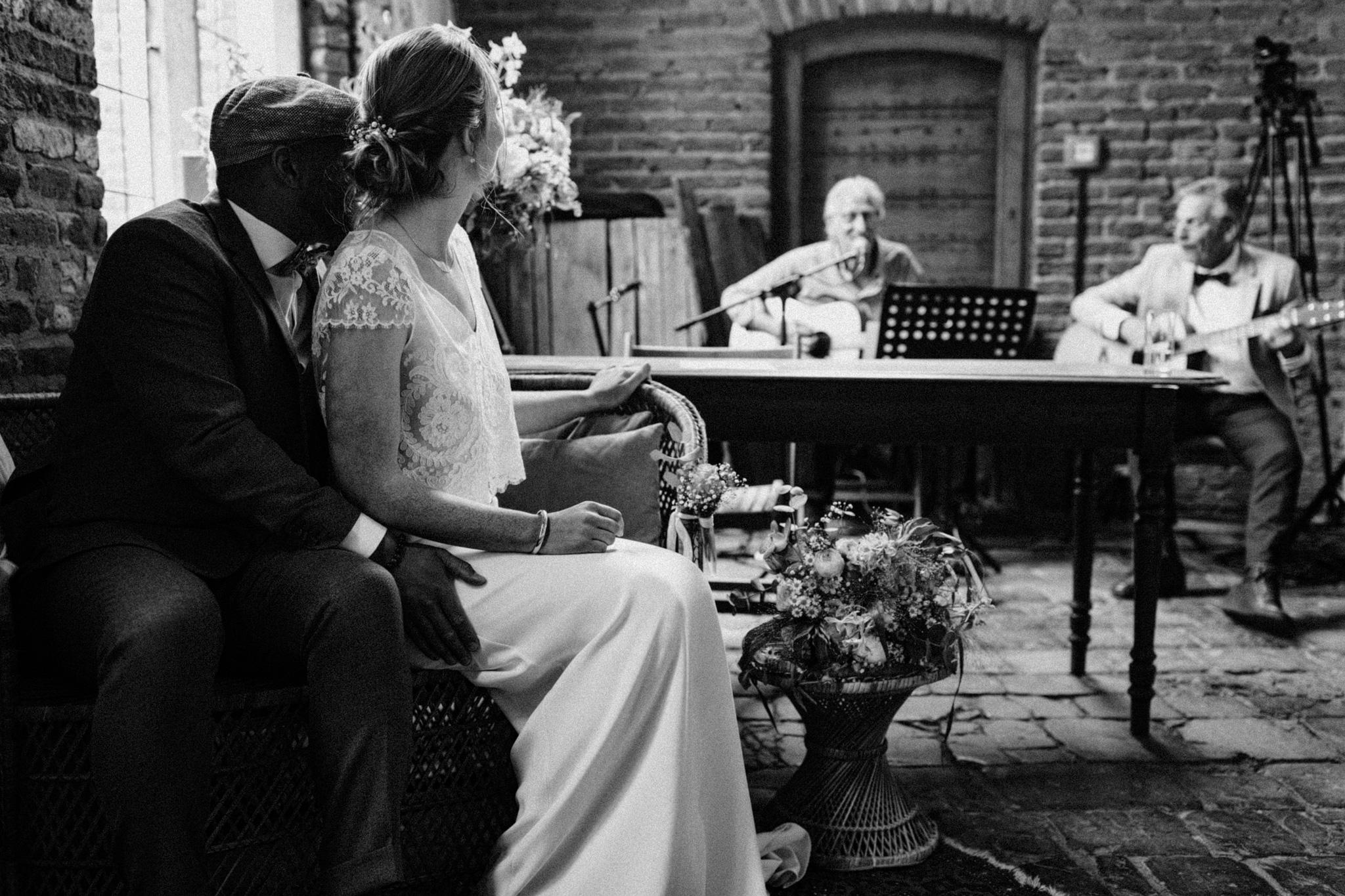 Bruid en bruidegom luisteren naar gitaarmuziek tijdens trouwceremonie Kloster Graefenthal
