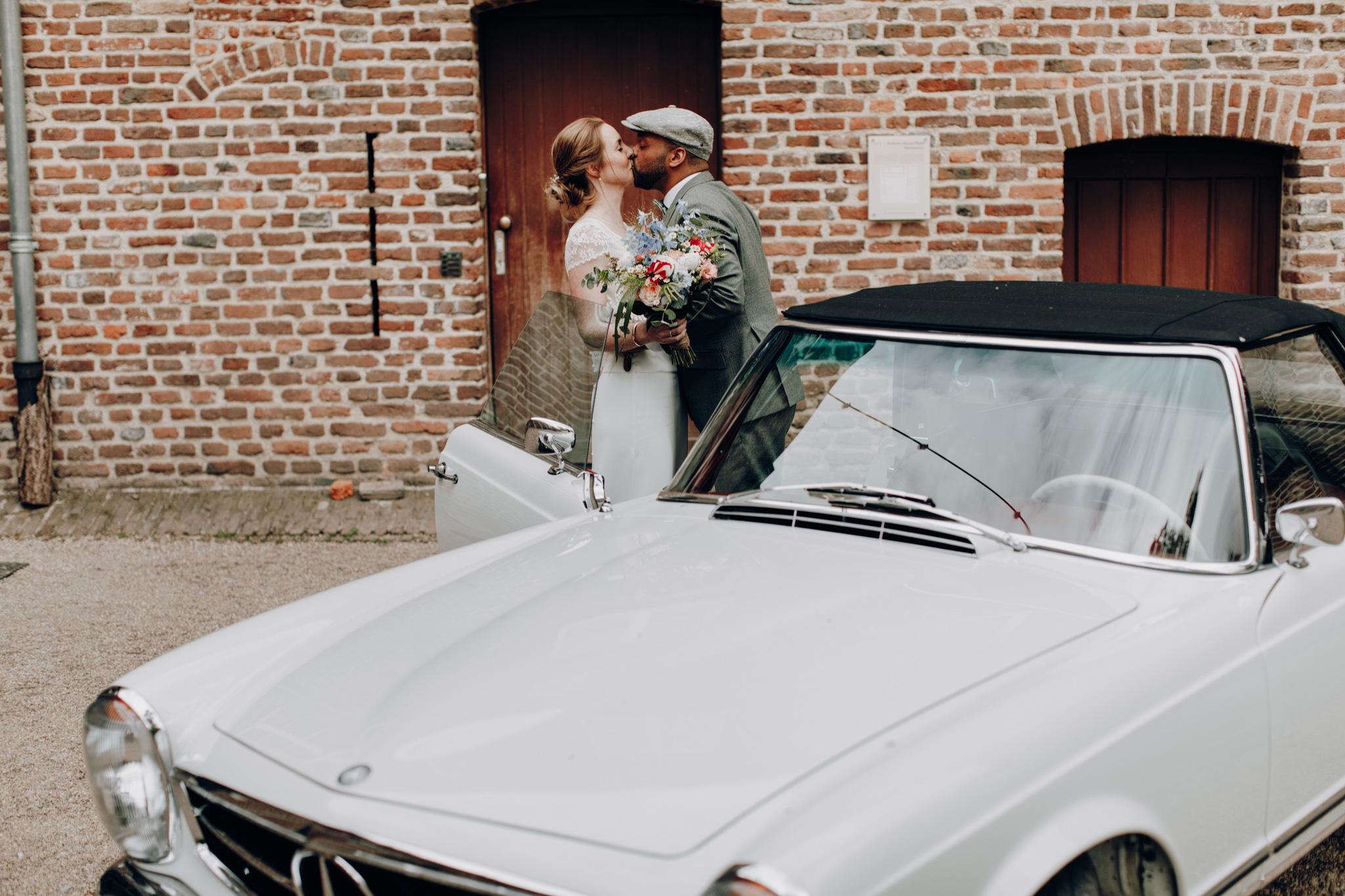 Bruid en bruidegom kussen voor trouwauto bij Kloster Graefenthal