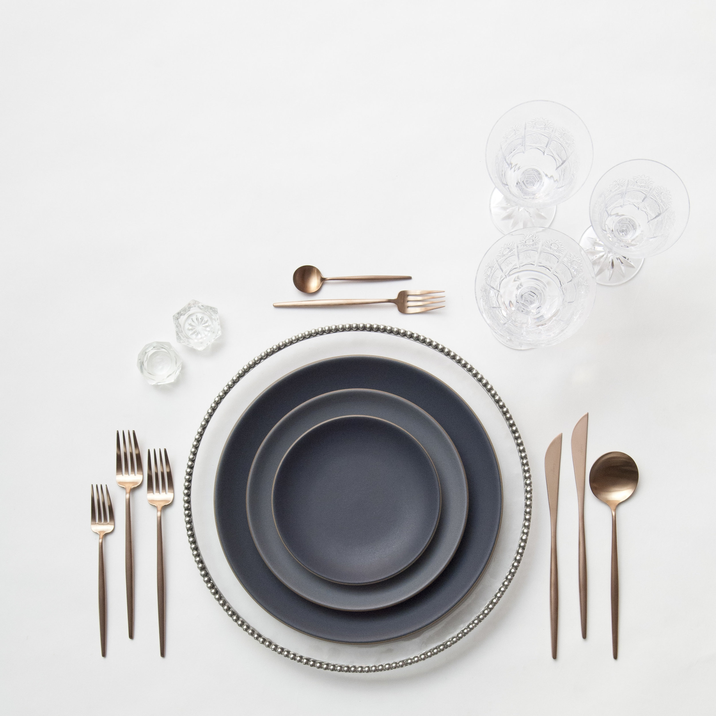 RENT: Pavé Glass Chargers in Pewter + Heath Ceramics in Indigo/Slate + Moon Flatware in Brushed Rose Gold + Czech Crystal Stemware + Antique Crystal Salt Cellars  SHOP: Moon Flatware in Brushed Rose Gold