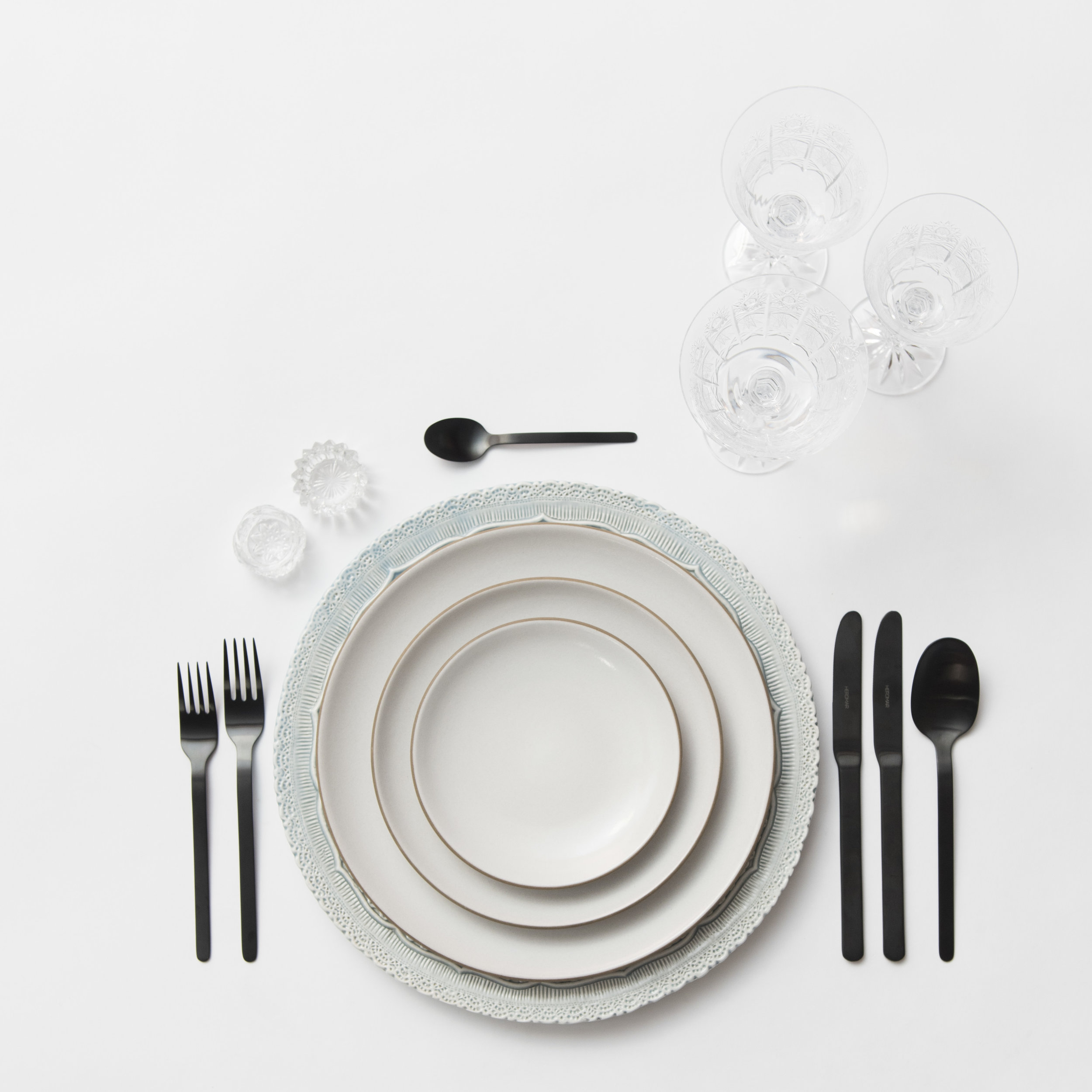 RENT: Lace Chargers in Dusty Blue + Heath Ceramics in Opaque White + Finn Flatware in Matte Black + Czech Crystal Stemware + Antique Crystal Salt Cellars