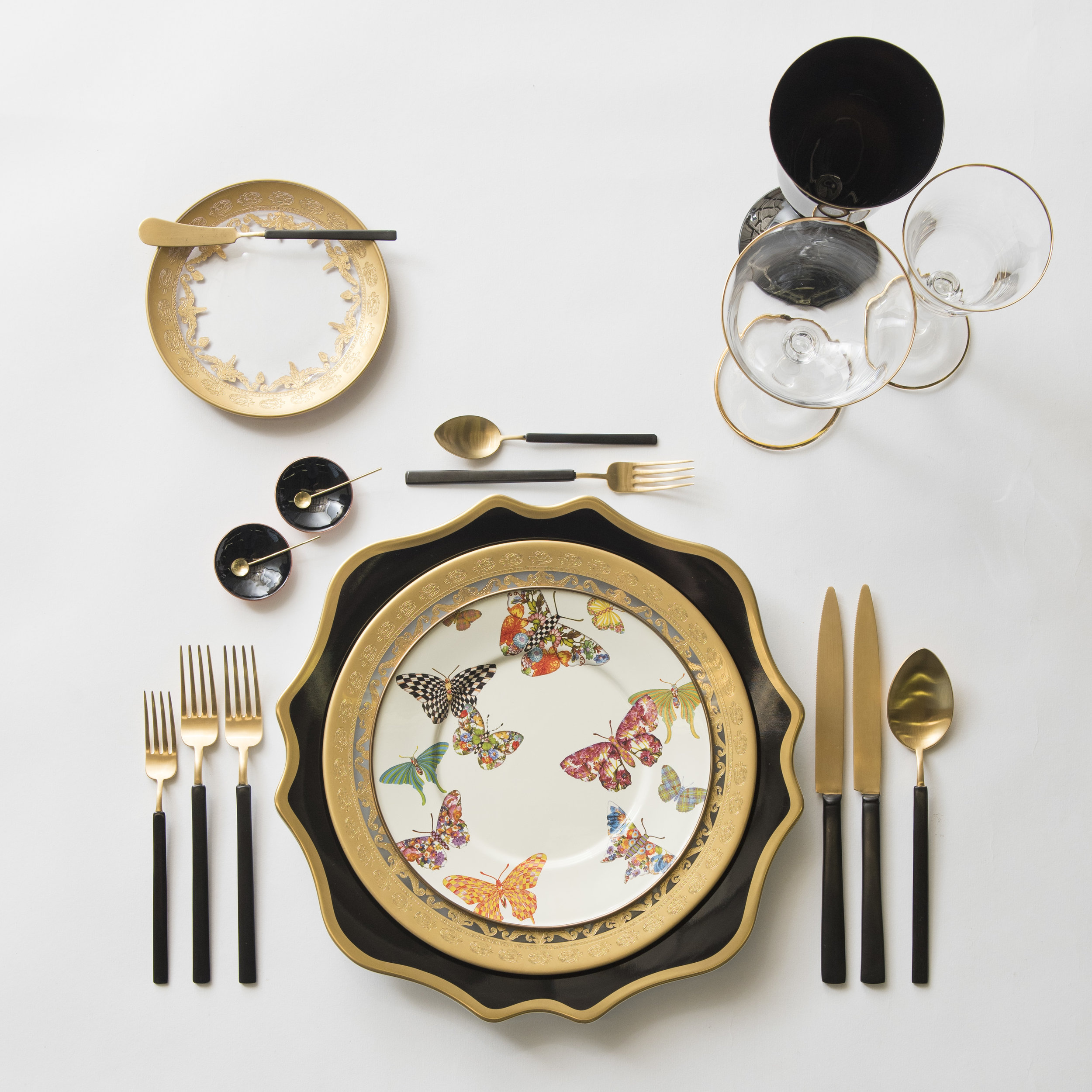 RENT: Anna Weatherley Chargers in Black/Gold + Versailles Glass Dinnerware in 24k Gold + MacKenzie-Childs Butterfly Garden Collection + Axel Flatware in Matte 24k Gold/Black + Chloe 24k Gold Rimmed Stemware + Chloe 24k Gold Rimmed Goblet in Black + Black Enamel Salt Cellars + Tiny Gold Spoons   SHOP: Chloe 24k Gold Rimmed Stemware + Black Enamel Salt Cellars + Tiny Gold Spoons