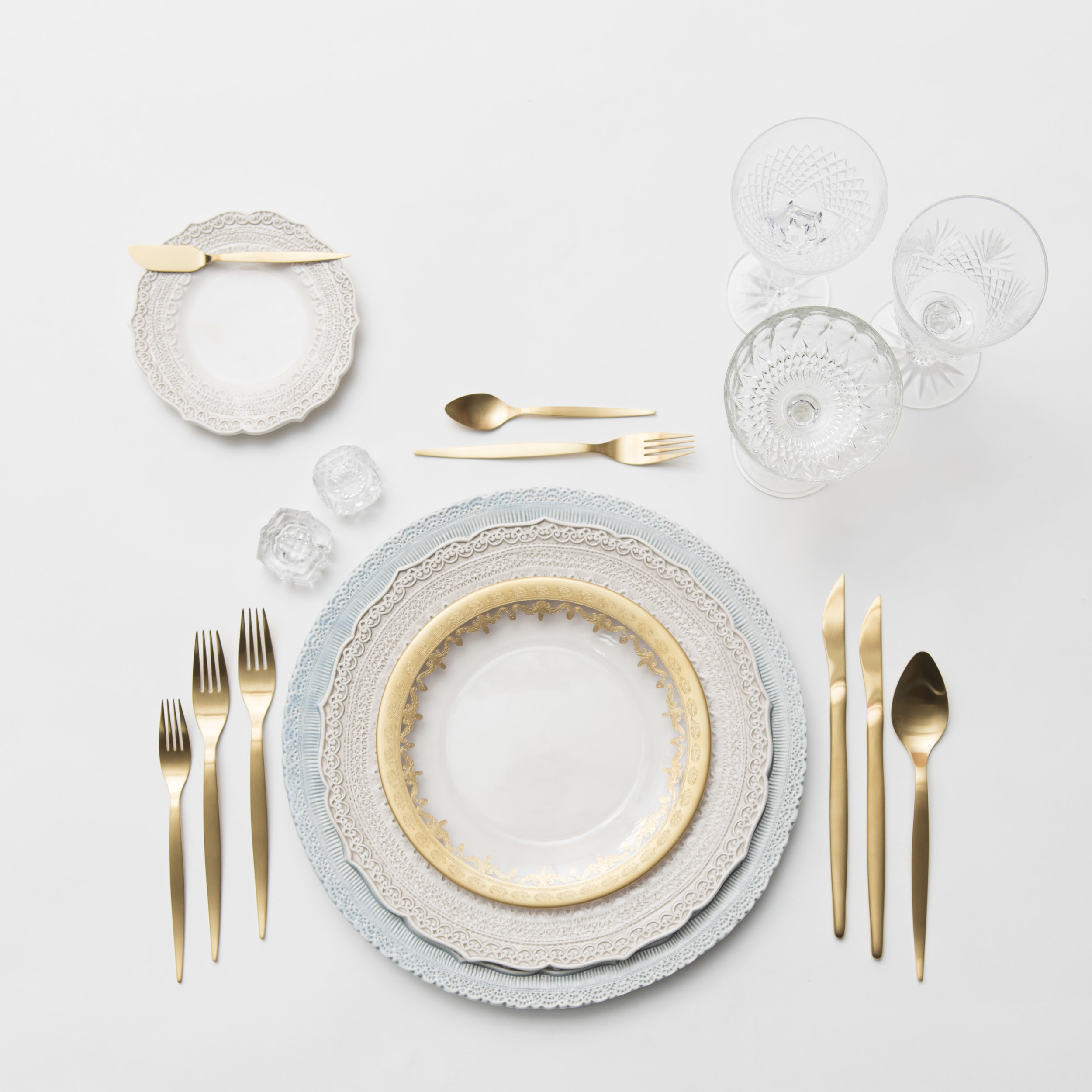 RENT: Lace Chargers in Dusty Blue + Lace Dinnerware in White + Versailles Glass Dinnerware in 24k Gold + Celeste Flatware in Matte Gold + Vintage Cut Crystal Goblets +Vintage Champagne Coupes + Antique Crystal Salt Cellars