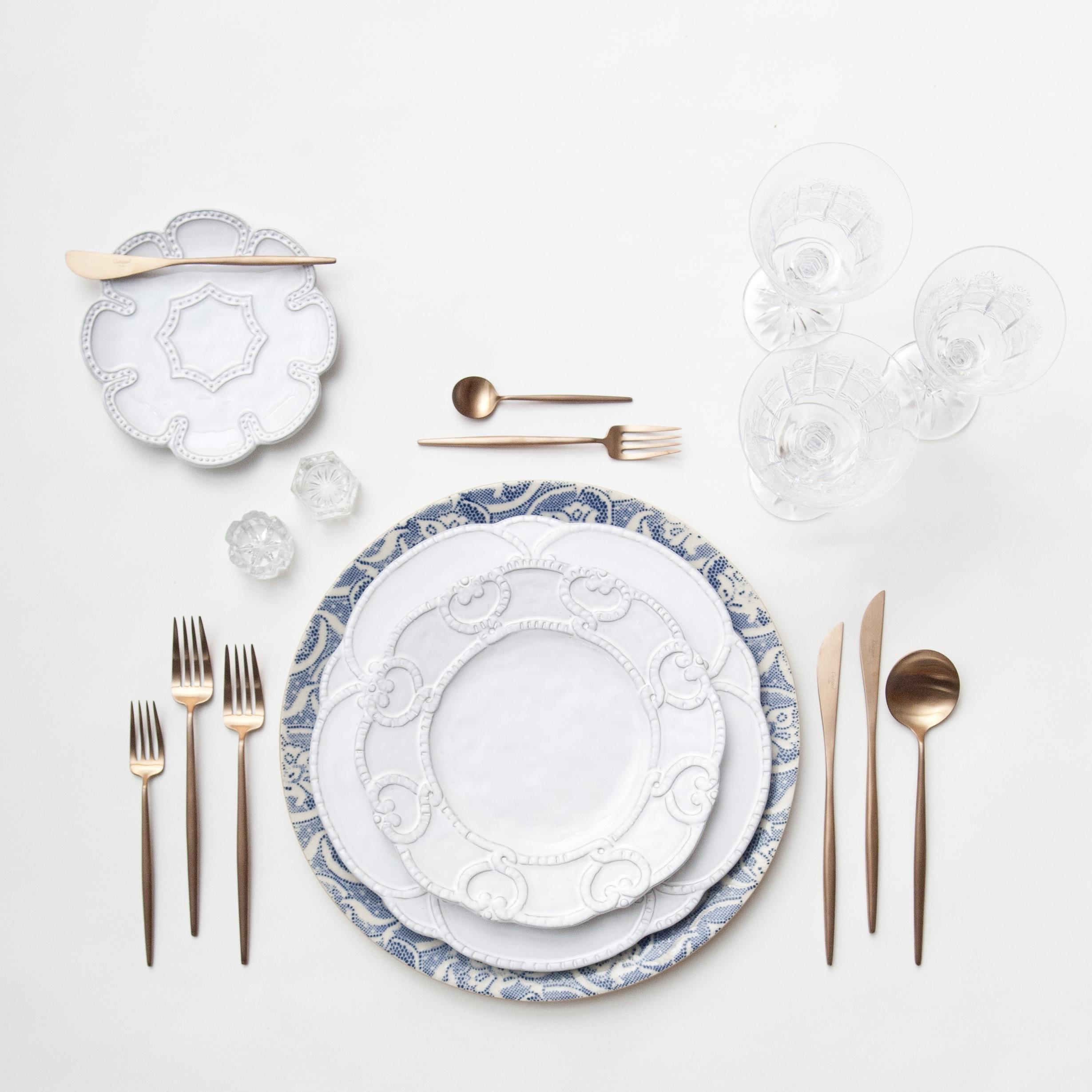 RENT: Blue Fleur de Lis Chargers + Signature Collection Dinnerware + Moon Flatware in Brushed Rose Gold + Czech Crystal Stemware + Antique Crystal Salt Cellars  SHOP:Moon Flatware in Brushed Rose Gold
