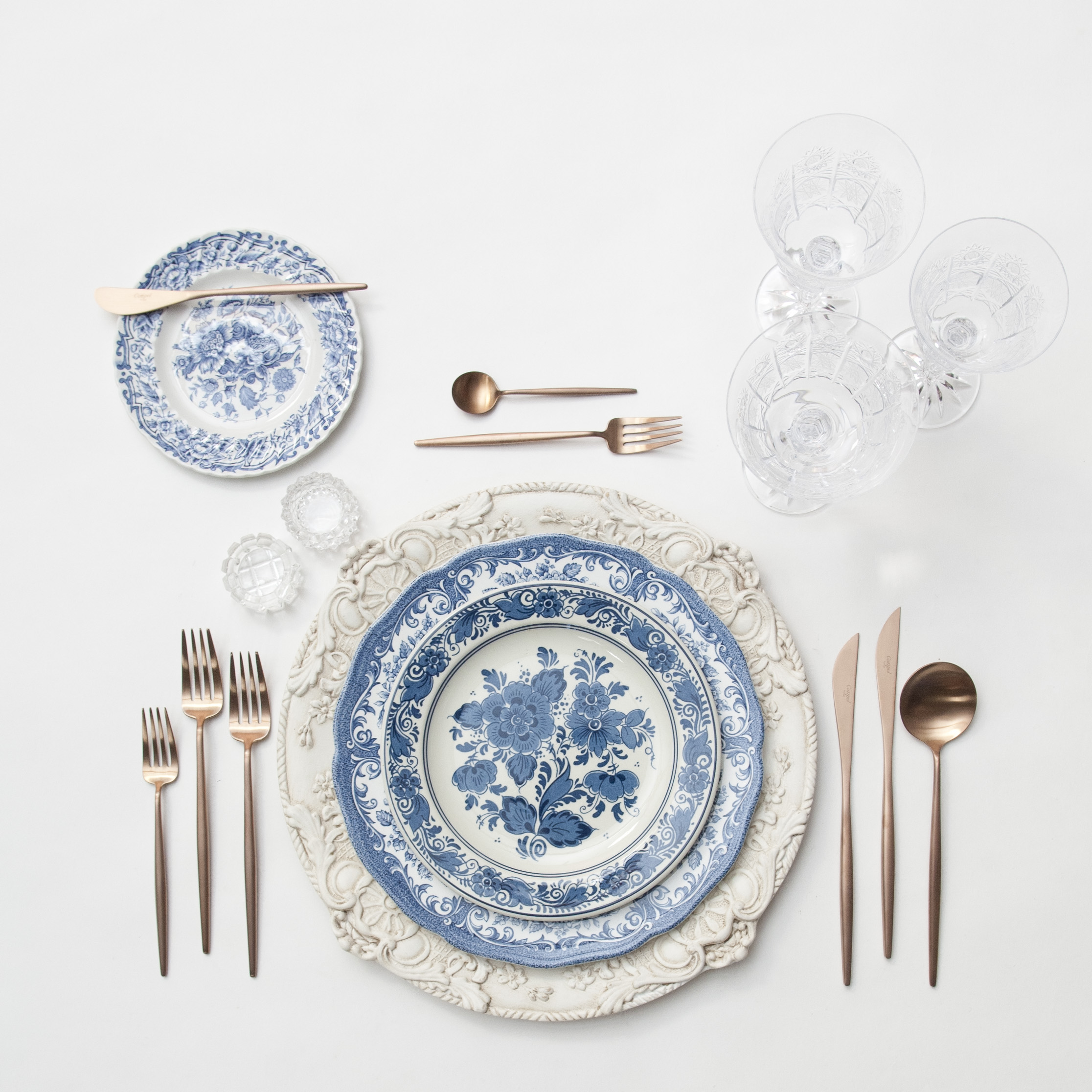 RENT: Verona Chargers in Antique White + Blue Garden Collection Vintage China + Moon Flatware in Brushed Rose Gold + Czech Crystal Stemware + Antique Crystal Salt Cellars  SHOP:Moon Flatware in Brushed Rose Gold