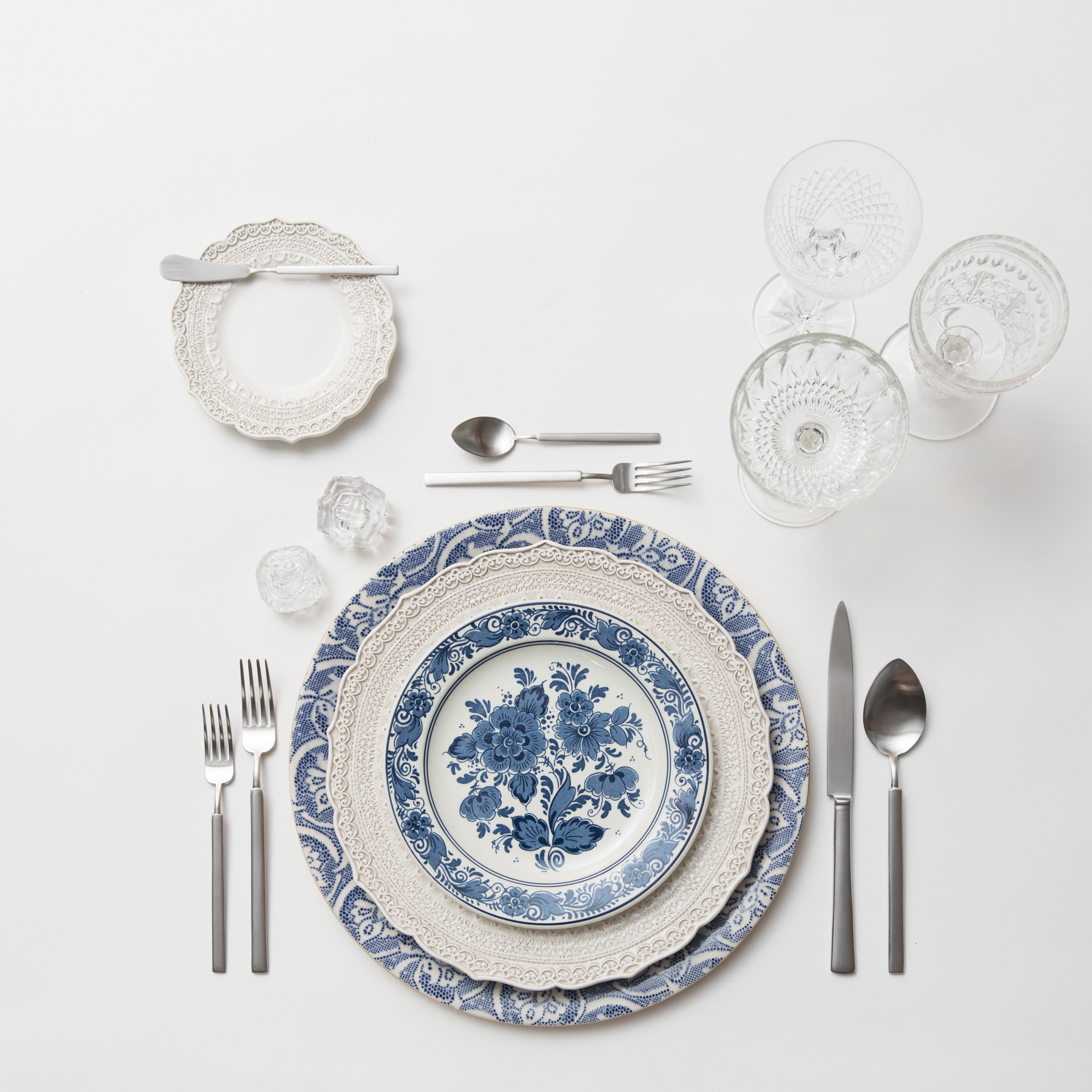 RENT: Blue Fleur de Lis Chargers + Lace Dinnerware in White + Blue Garden Collection Vintage China + Axel Flatware in Matte Silver + Vintage Cut Crystal Goblets + Early American Pressed Glass Goblets + Vintage Champagne Coupes + Antique Crystal Salt Cellars