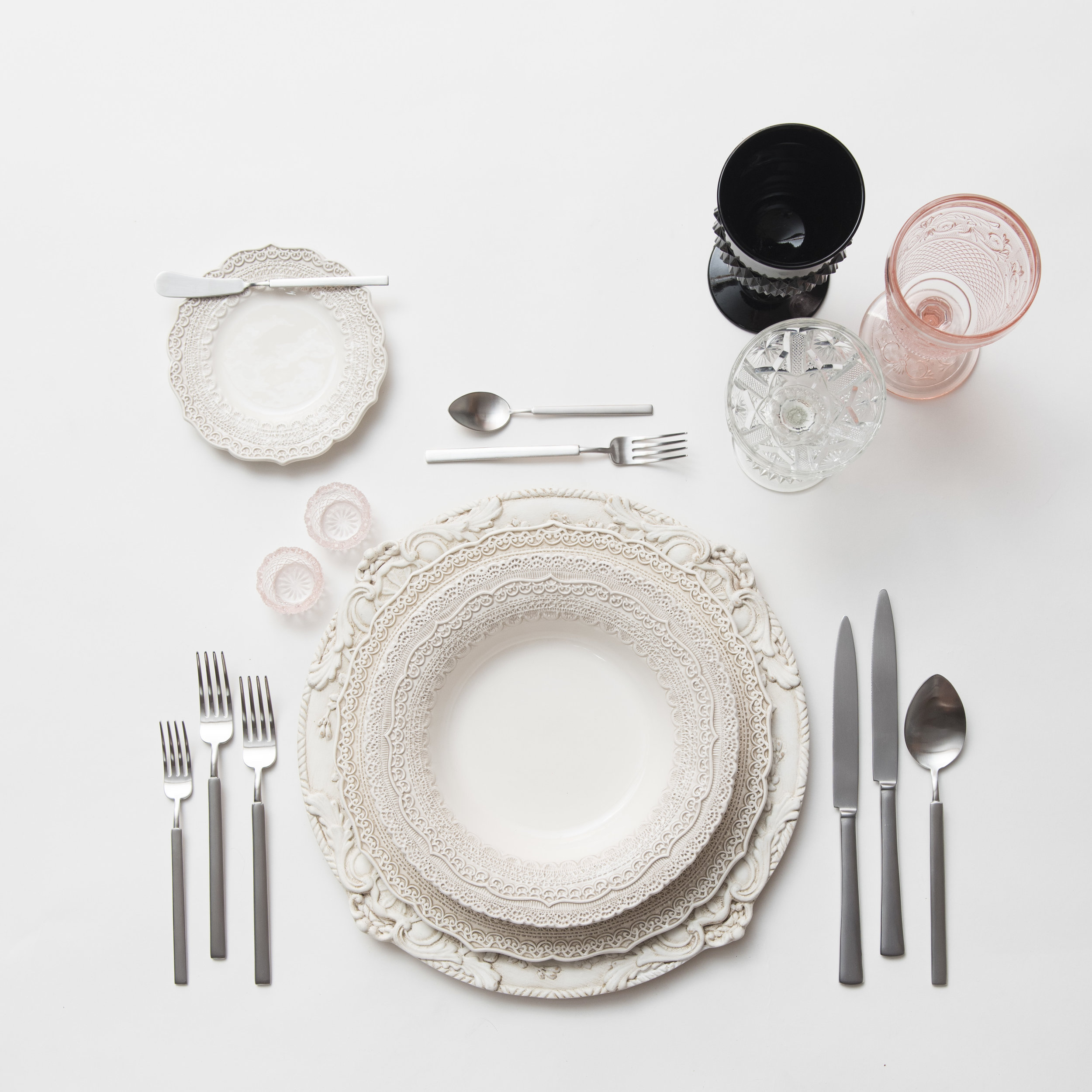 RENT: Verona Chargers in Antique White + Lace Dinnerware in White + Axel Flatware in Matte Silver + Black/Pink Vintage Goblets + Vintage Champagne Coupe + Pink Crystal Salt Cellars  SHOP:Verona Chargers in Antique White