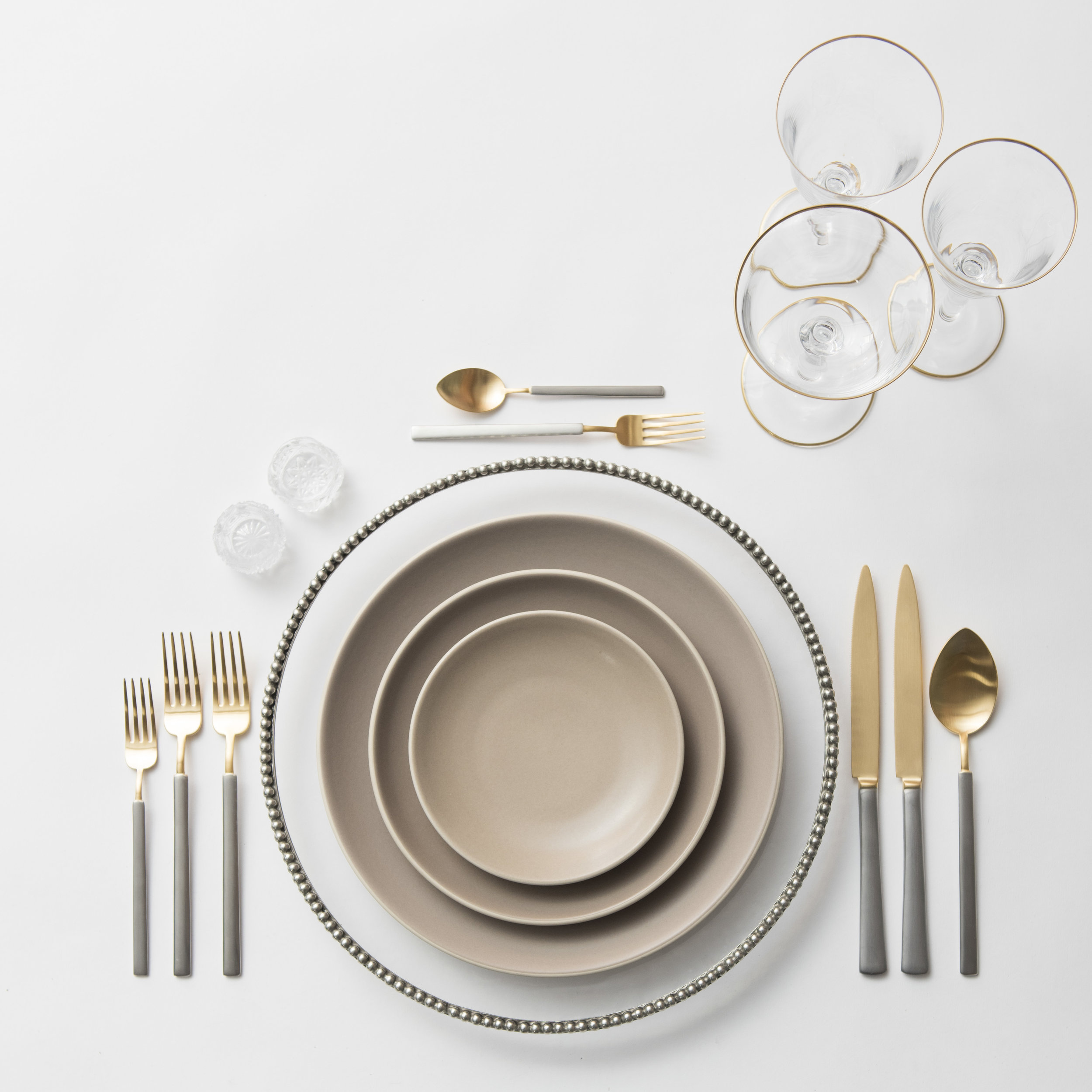 RENT: Pav é Glass Chargers in Pewter  + Heath Ceramics in French Grey + Axel Flatware in Matte 24k Gold/Silver + Chloe 24k Gold Rimmed Stemware + Antique Crystal Salt Cellars  SHOP: Chloe 24k Gold Rimmed Stemware