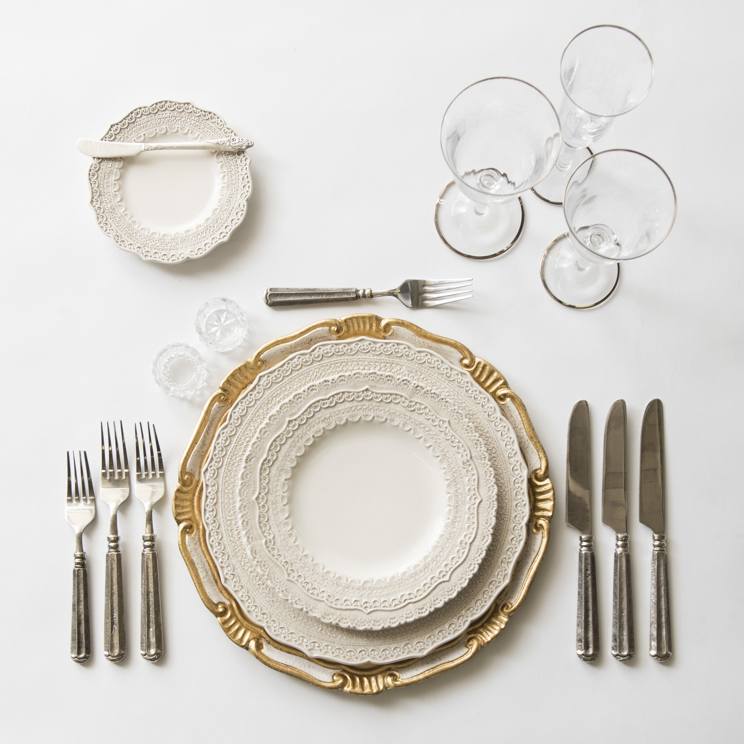 RENT: Florentine Chargers in White/Gold + Lace Dinnerware in White + Tuscan Flatware in Pewter + Chloe Platinum Rimmed Stemware + Antique Crystal Salt Cellars  SHOP:Florentine Chargers in White/Gold