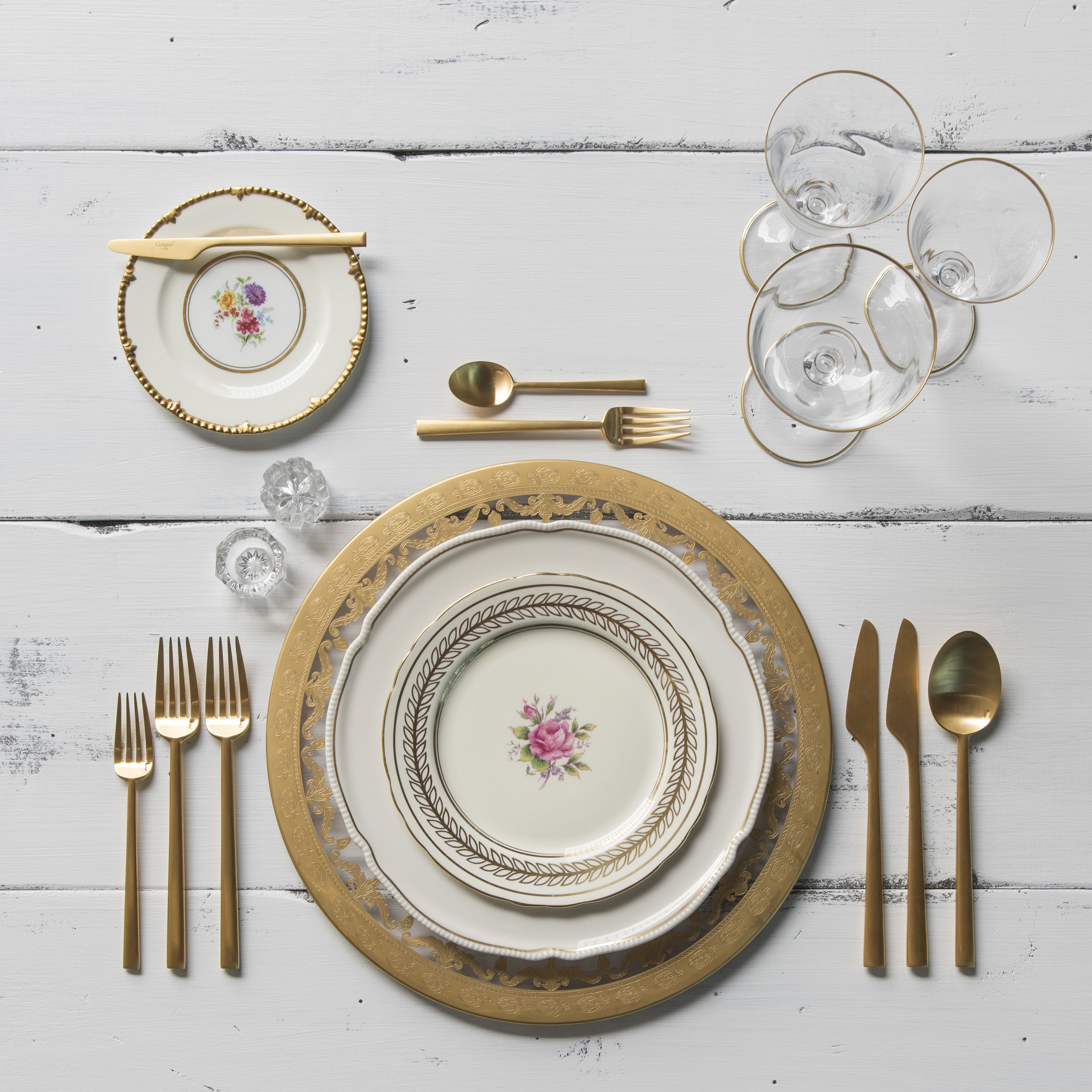RENT: Versailles Glass Chargers in 24k Gold + White Botanicals Vintage China + Rondo Flatware in Brushed 24k Gold + Chloe 24k Gold Rimmed Stemware + Antique Crystal Salt Cellars  SHOP:Rondo Flatware in Brushed 24k Gold + Chloe 24k Gold Rimmed Stemware