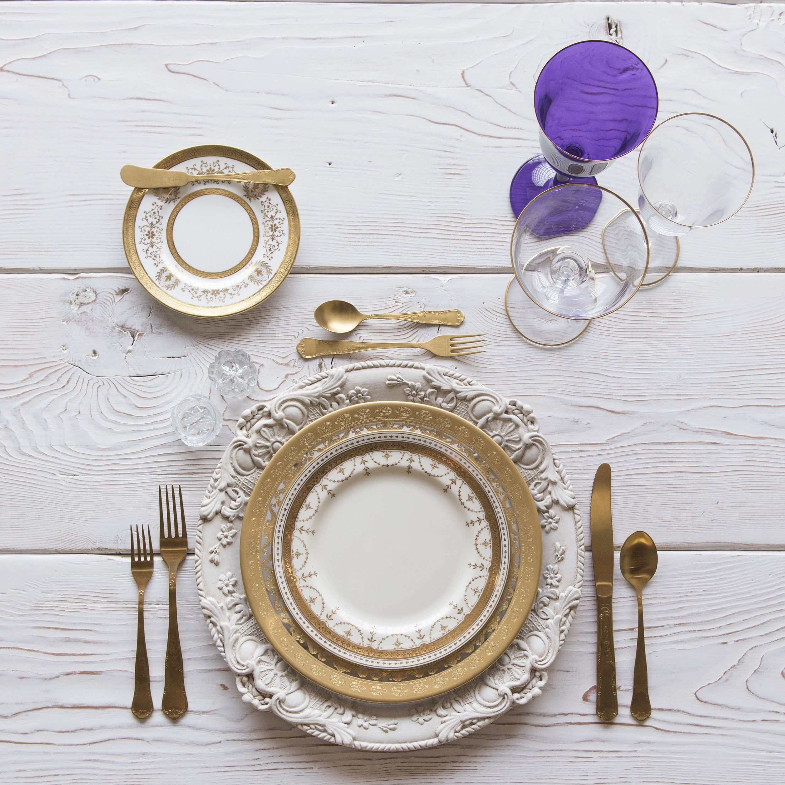 RENT: Verona Chargers in Antique White + Versailles Glass Dinnerware in 24k Gold + Crown Gold Collection Vintage China + Chateau Flatware in Matte Gold + Chloe 24k Gold Rimmed Stemware + Chloe 24k Gold Rimmed Goblet in Purple + Antique Crystal Salt Cellars  SHOP:Verona Chargers in Antique White +Chloe 24k Gold Rimmed Stemware