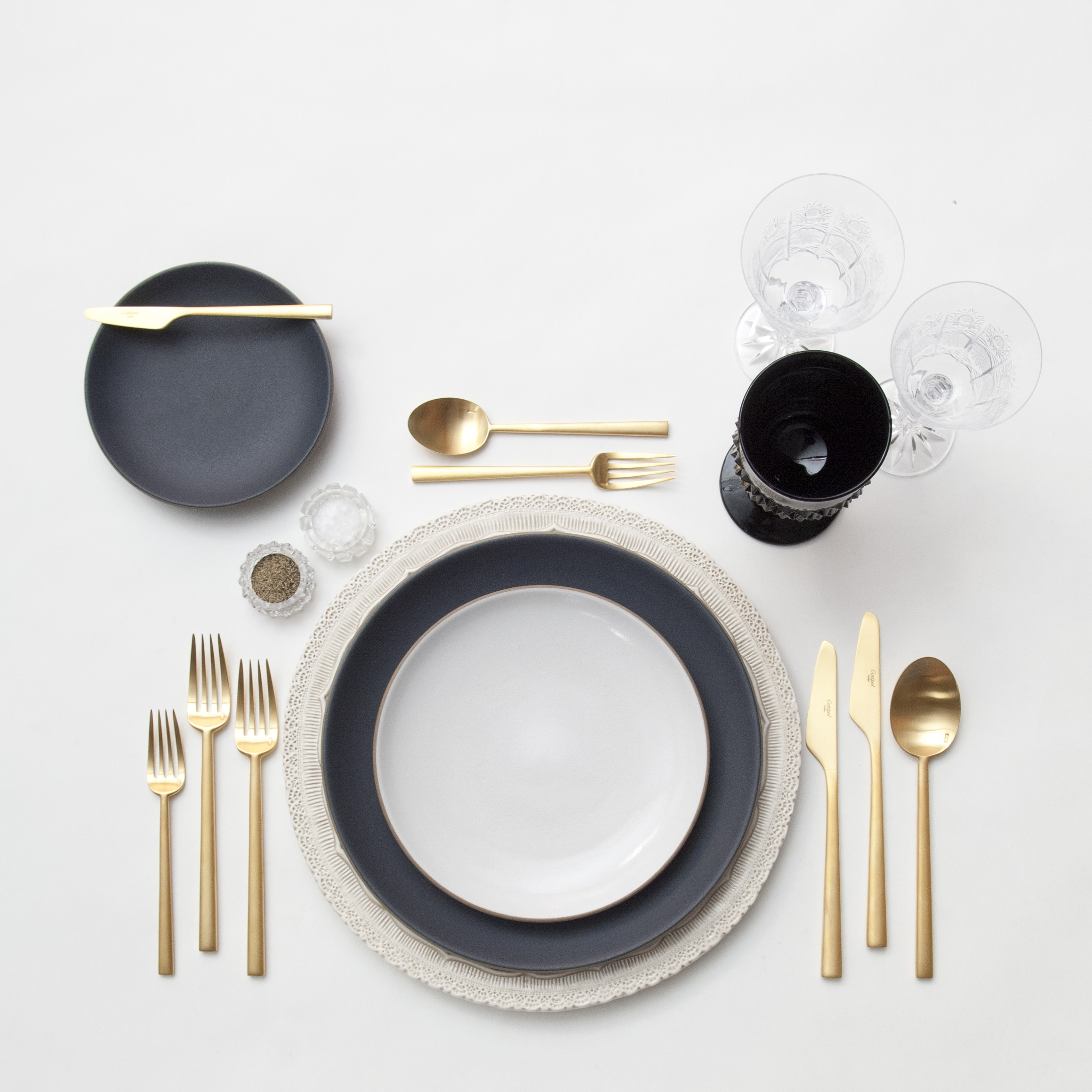 RENT: Lace Chargers in White + Heath Ceramics in Indigo/Slate/Opaque White + Rondo Flatware in Brushed 24k Gold + Czech Crystal Stemware + Vintage Black Goblets + Antique Crystal Salt Cellars   SHOP: Rondo Flatware in Brushed 24k Gold