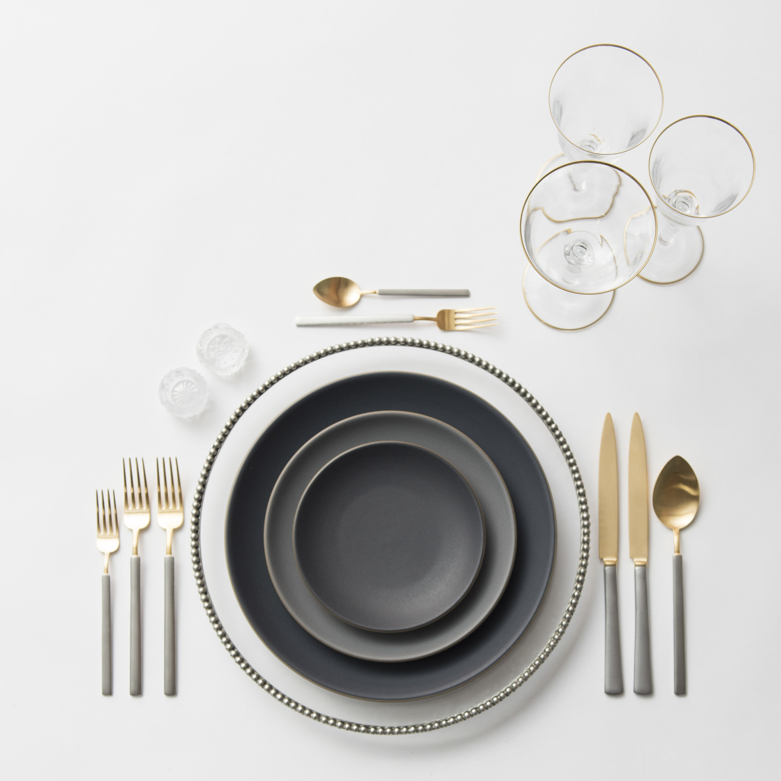 RENT: Pav é Glass Chargers in Pewter  + Heath Ceramics in Indigo/Slate + Axel Flatware in Matte 24k Gold/Silver + Chloe 24k Gold Rimmed Stemware + Antique Crystal Salt Cellars  SHOP: Chloe 24k Gold Rimmed Stemware