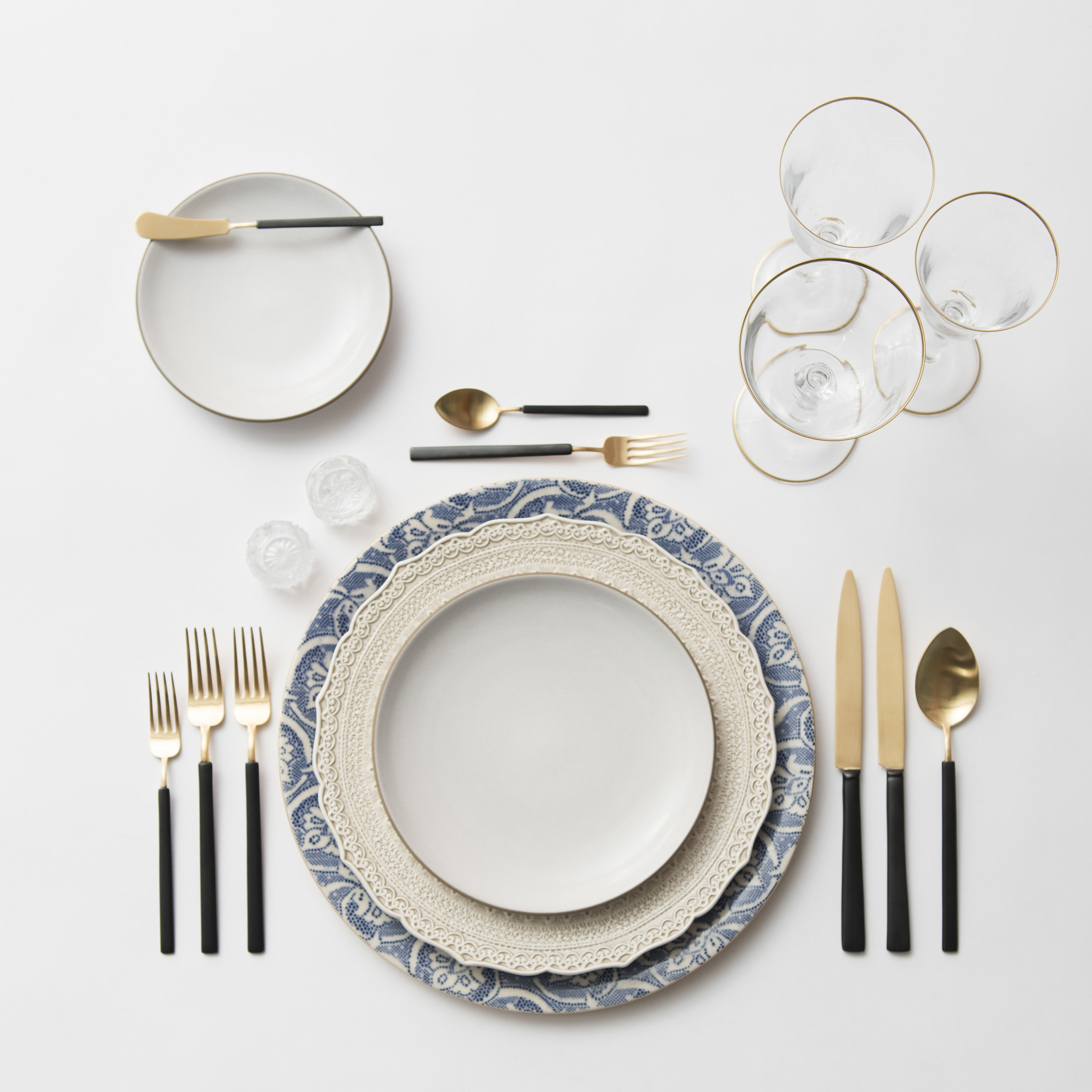 RENT: Blue Fleur de Lis Chargers + Lace Dinnerware in White + Heath Ceramics in Opaque White + Axel Flatware in Matte 24k Gold/Black + Chloe 24k Gold Rimmed Stemware + Antique Crystal Salt Cellars  SHOP: Chloe 24k Gold Rimmed Stemware