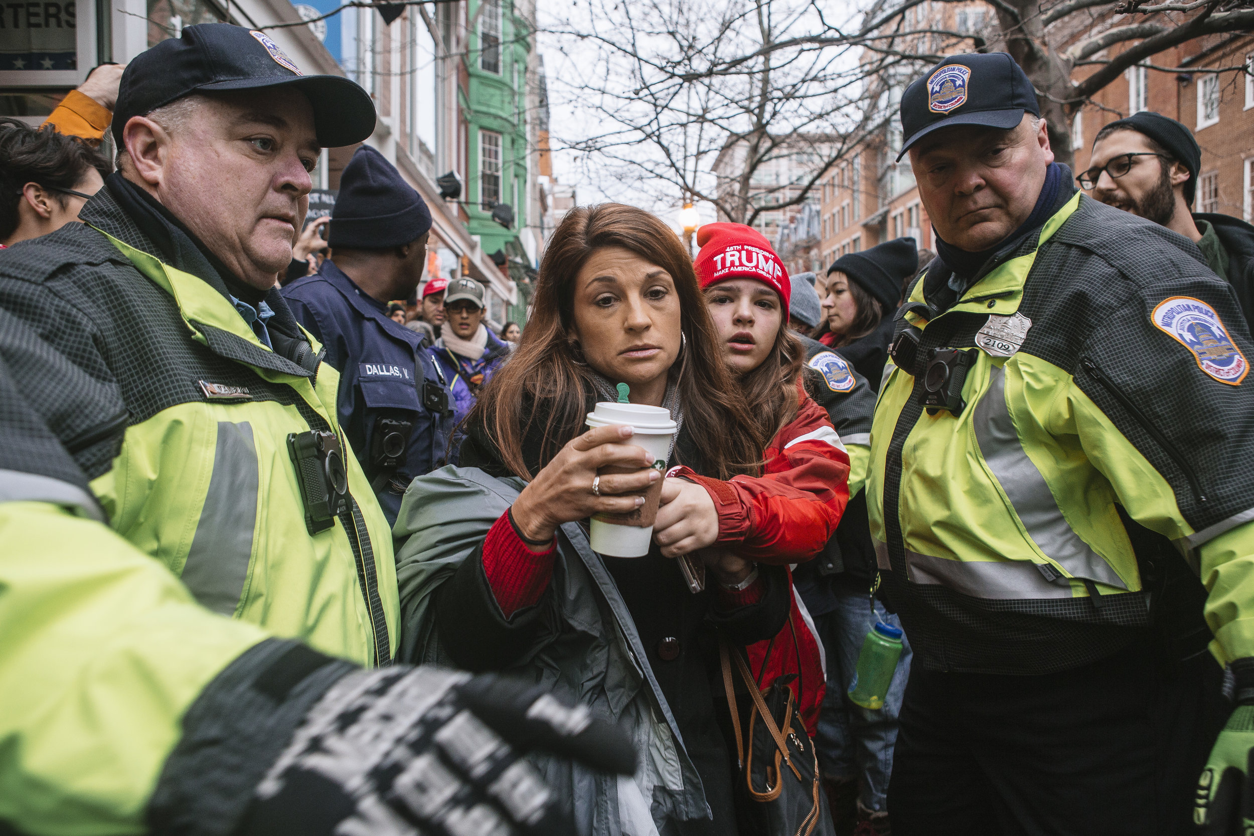 A mother and her daughter are escorted by the police through a blockade at the entrance to the 2017 US Presidential Inauguration