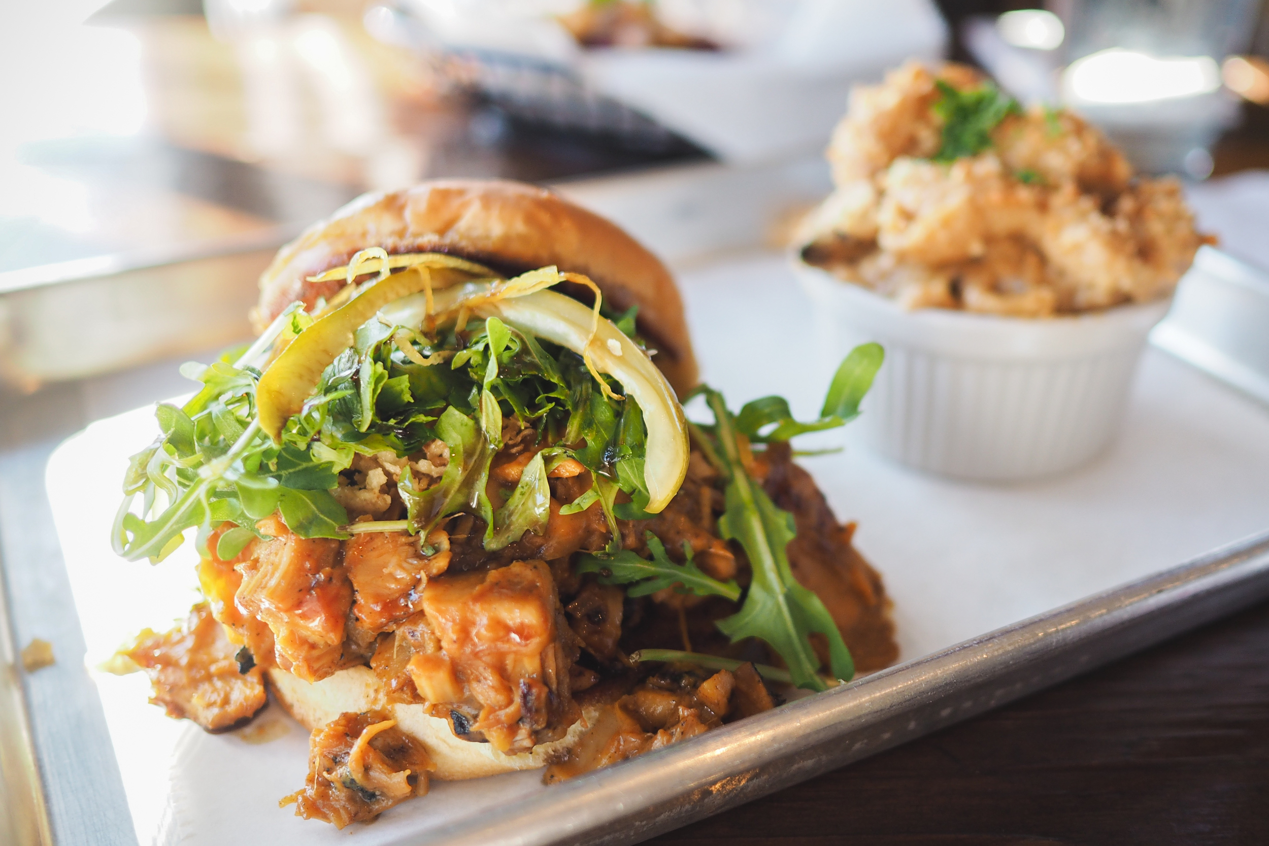 Pulled Carolina BBQ Jackfruit Sandwich: Jackfruit, fried onions, pickles, arugula, coca-cola redux, preserved lemon, and served on a bun.